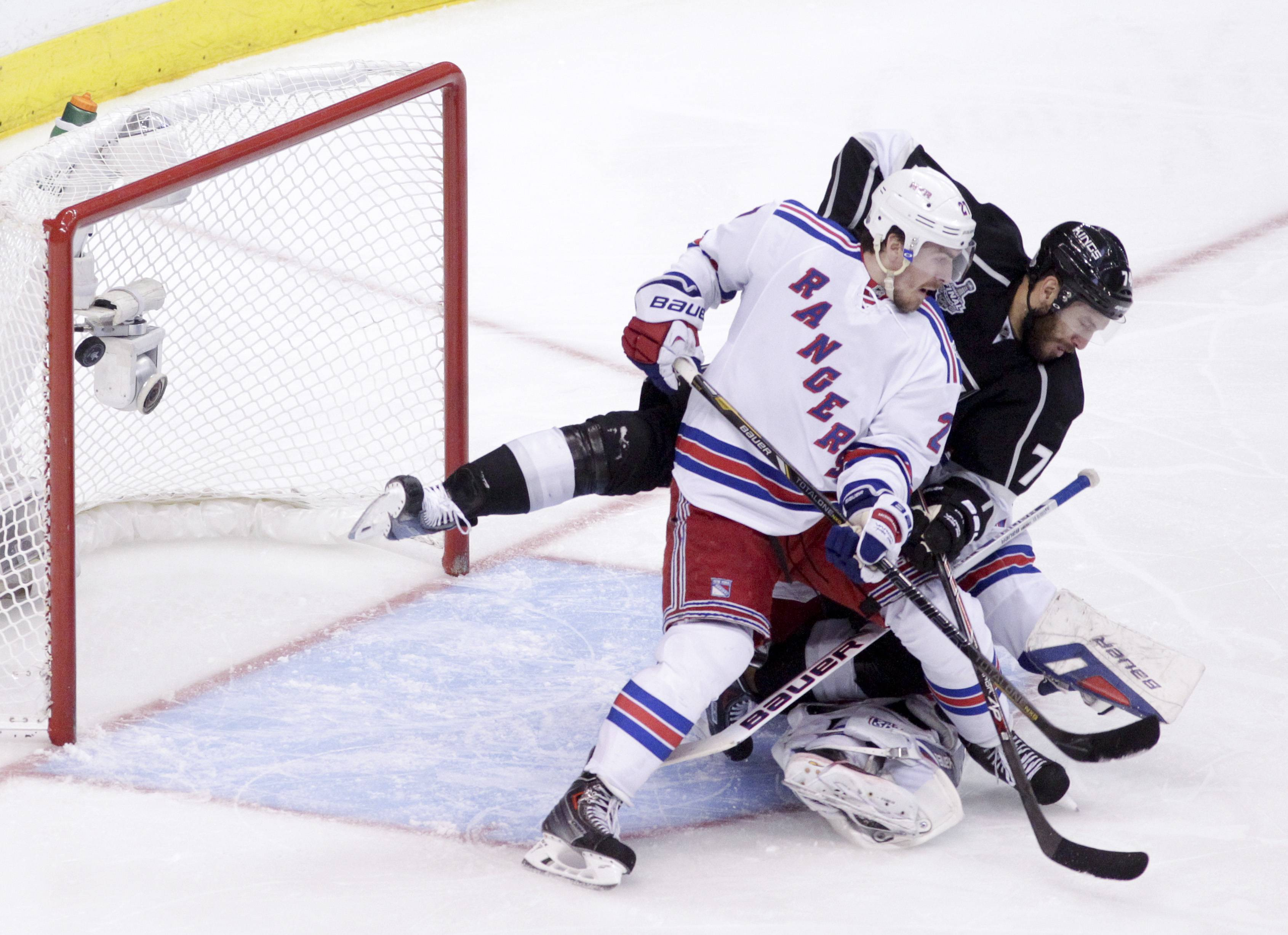 Los Angeles Kings left wing Dwight King, middle, scores between New York Rangers defenseman Ryan McDonagh, left, and goalie Henrik Lundqvist, of Sweden, during the third period of Game 2 Saturday in the NHL Stanley Cup Final hockey series in Los Angeles. NHL Commissioner Gary Bettman has announced that concussions are down across the league.
