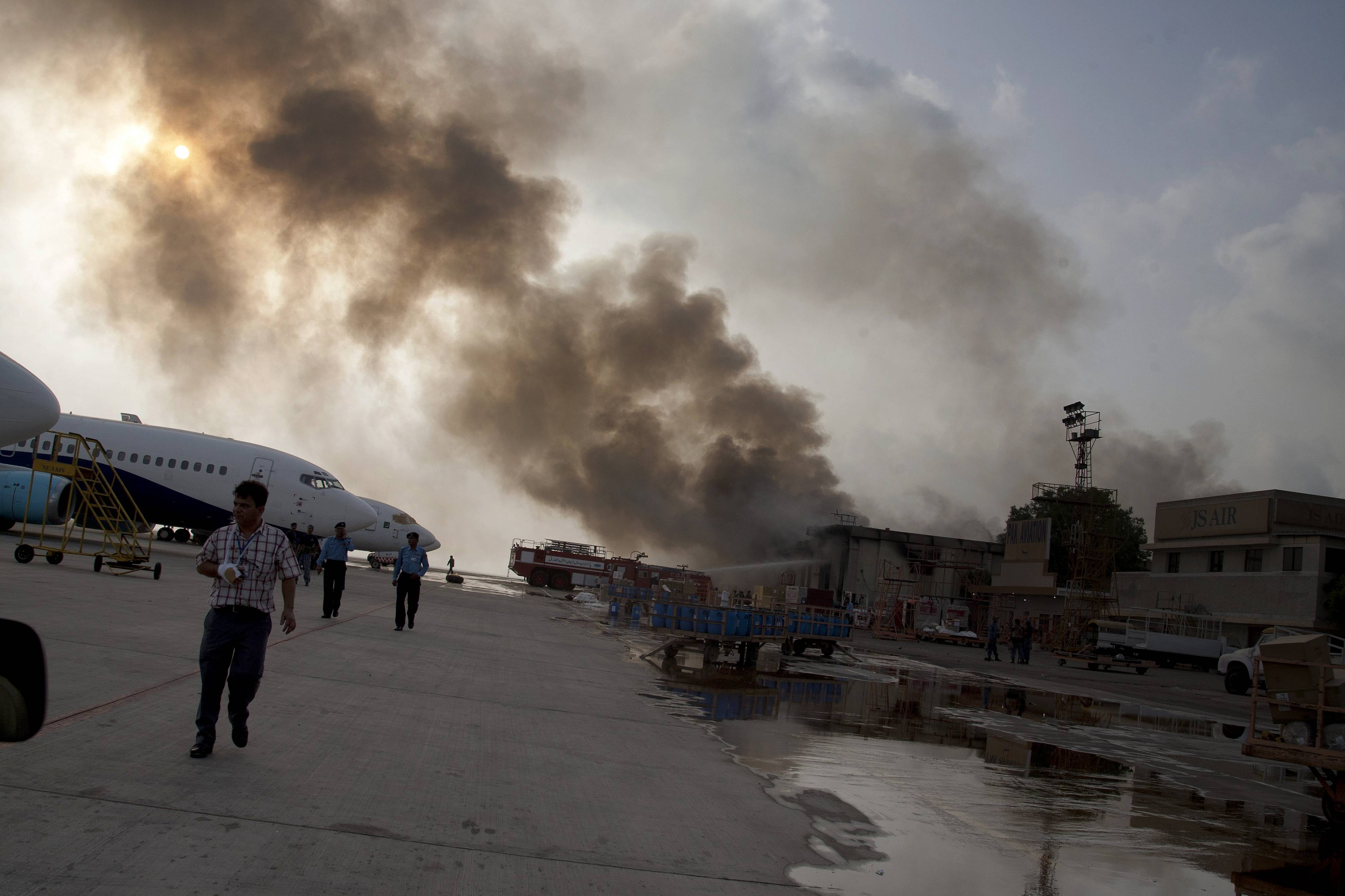 Smoke rises above Karachi airport terminal Monday, June 9, 2014 in Pakistan. Gunmen disguised as police guards attacked the terminal with machine guns and a rocket launcher during a five-hour siege that killed 13 people as explosions echoed into the night, while security forces retaliated and killed all the attackers, officials said Monday.