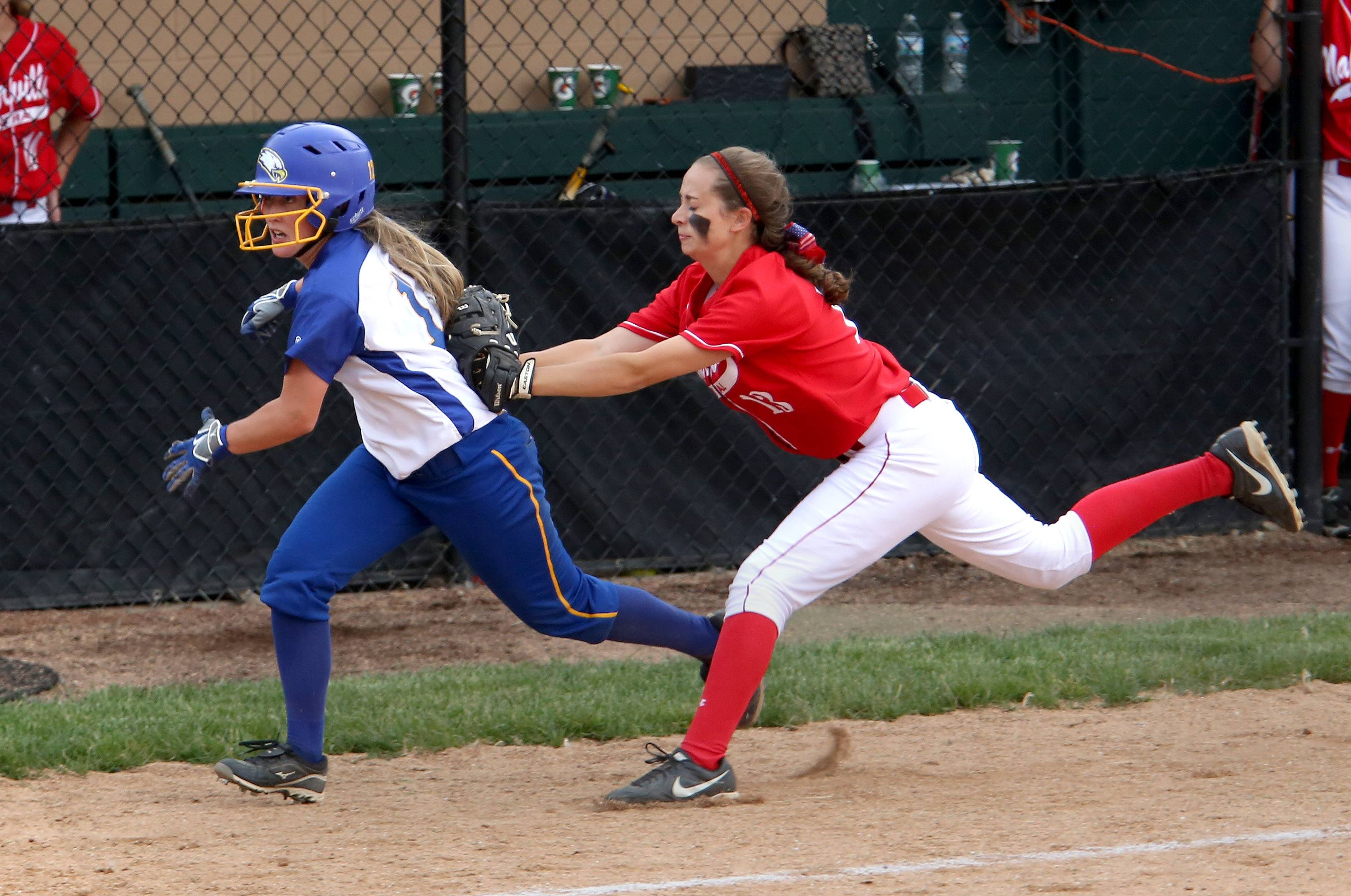 Naperville Central's Courtney Giebel, right, tags out Brianna Soltis of Sandburg, left, after she got caught between third base and home plate in the 6th inning during Class 4A supersectional softball at North Central College in Naperville on Monday.