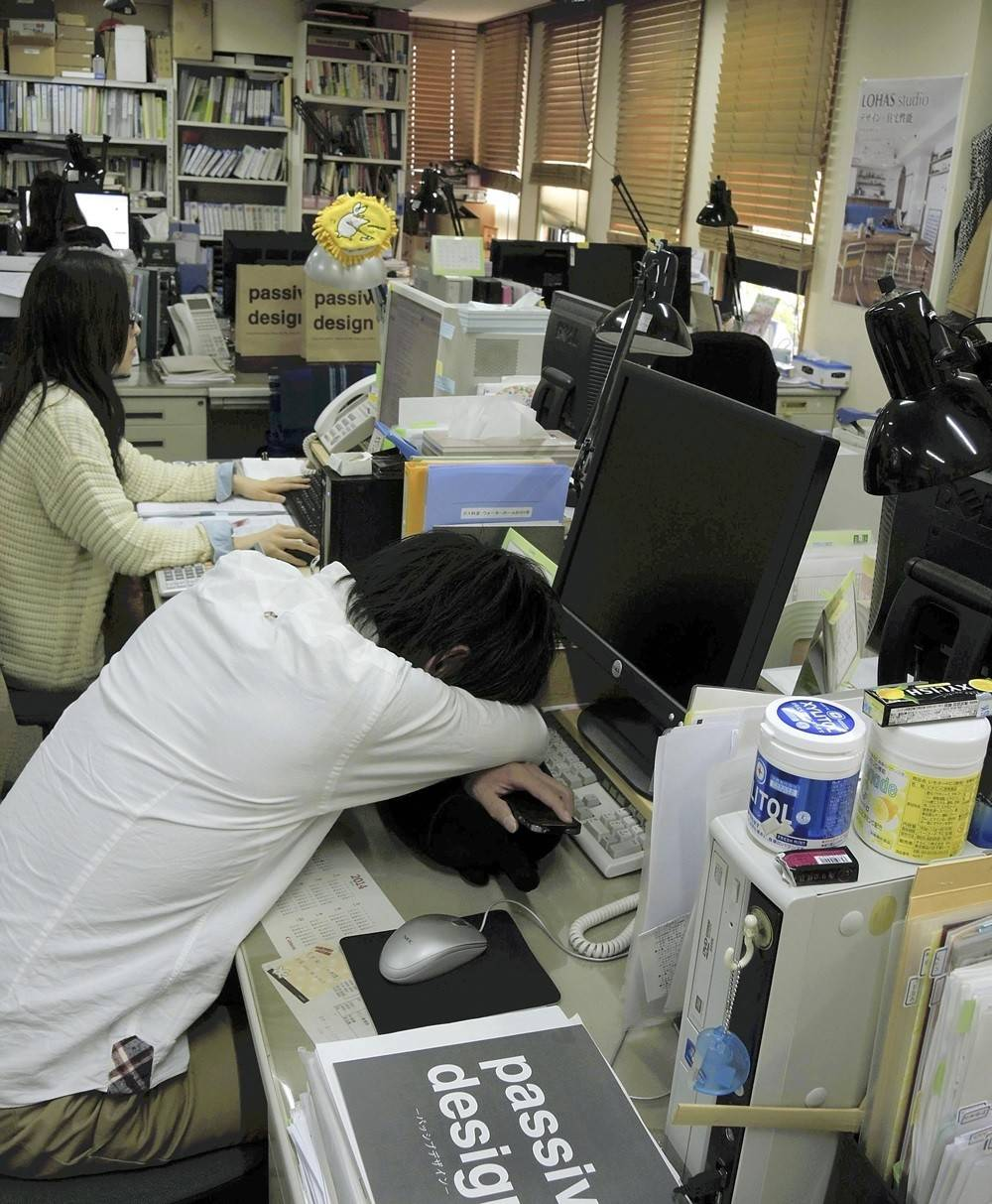 An employee of Okuta Corp. in Saitama takes a nap at his desk during work hours using the company's power-nap system.