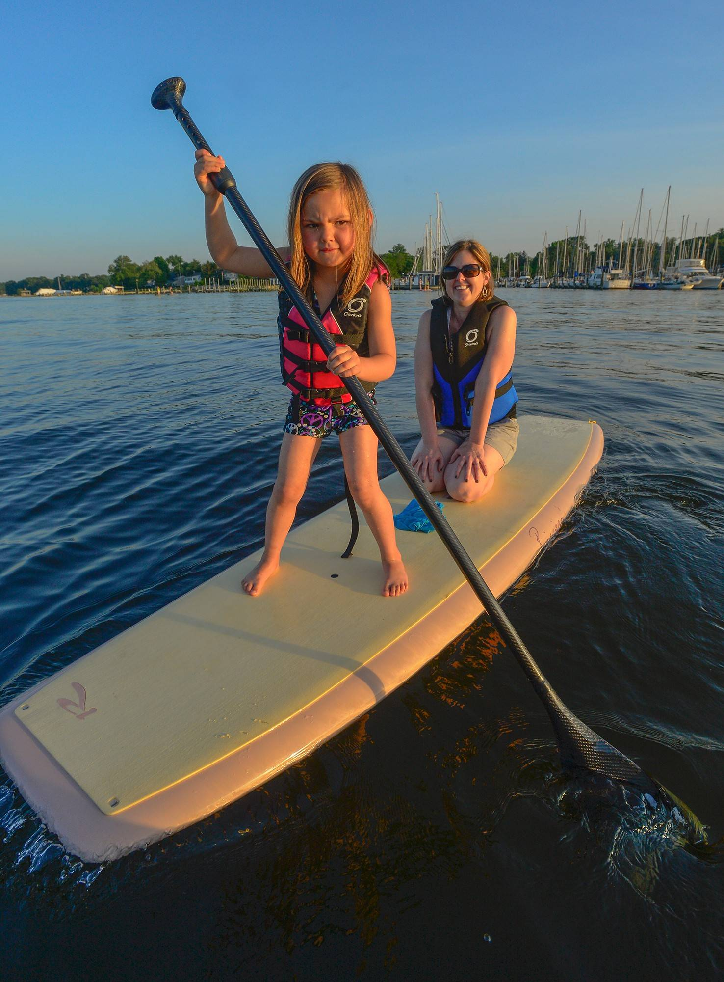 Five-year-old Cate Gelderman gives her mom, Bridget Gelderman, a break from paddling during a free community stand-up paddle class with adults and kids on the Magothy River near Arnold, Md.