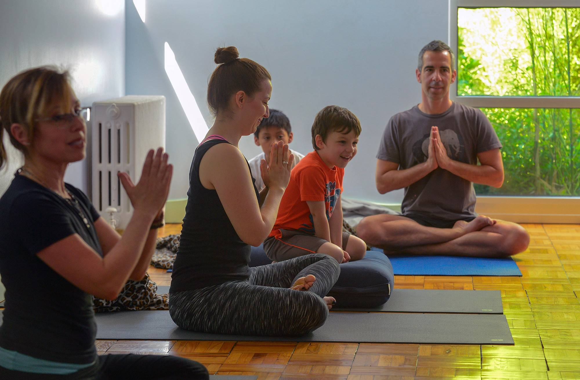 Linda Feldman, left, leads a family class at Circle Yoga in Washington. Elias OíKeefe and mom Deanna Ortiz, center, and Tristan Eckert and dad Christopher Sperl participate.