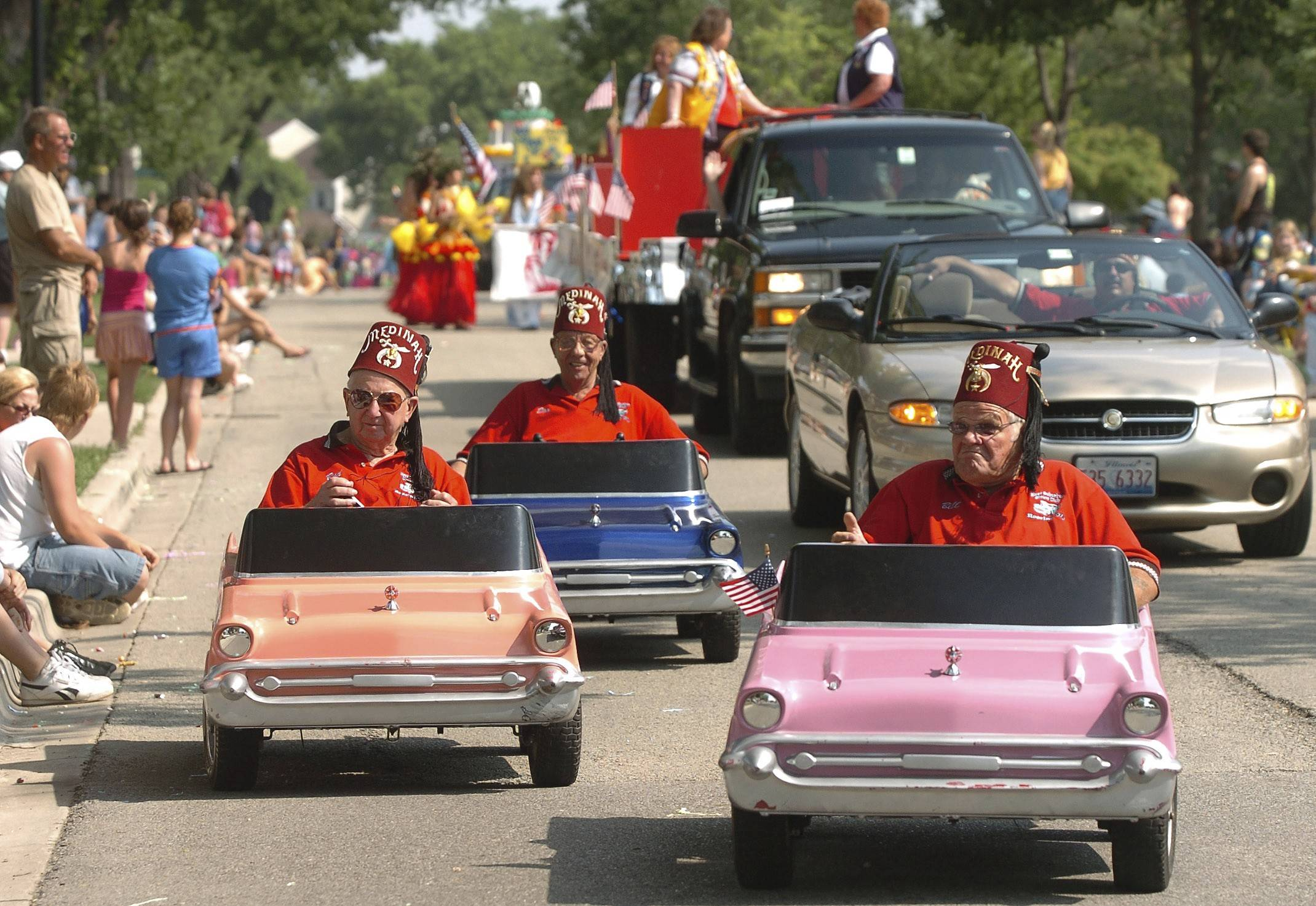 Mini cars amuse people at the 2006 edition of the Elk Grove Village Hometown Parade.