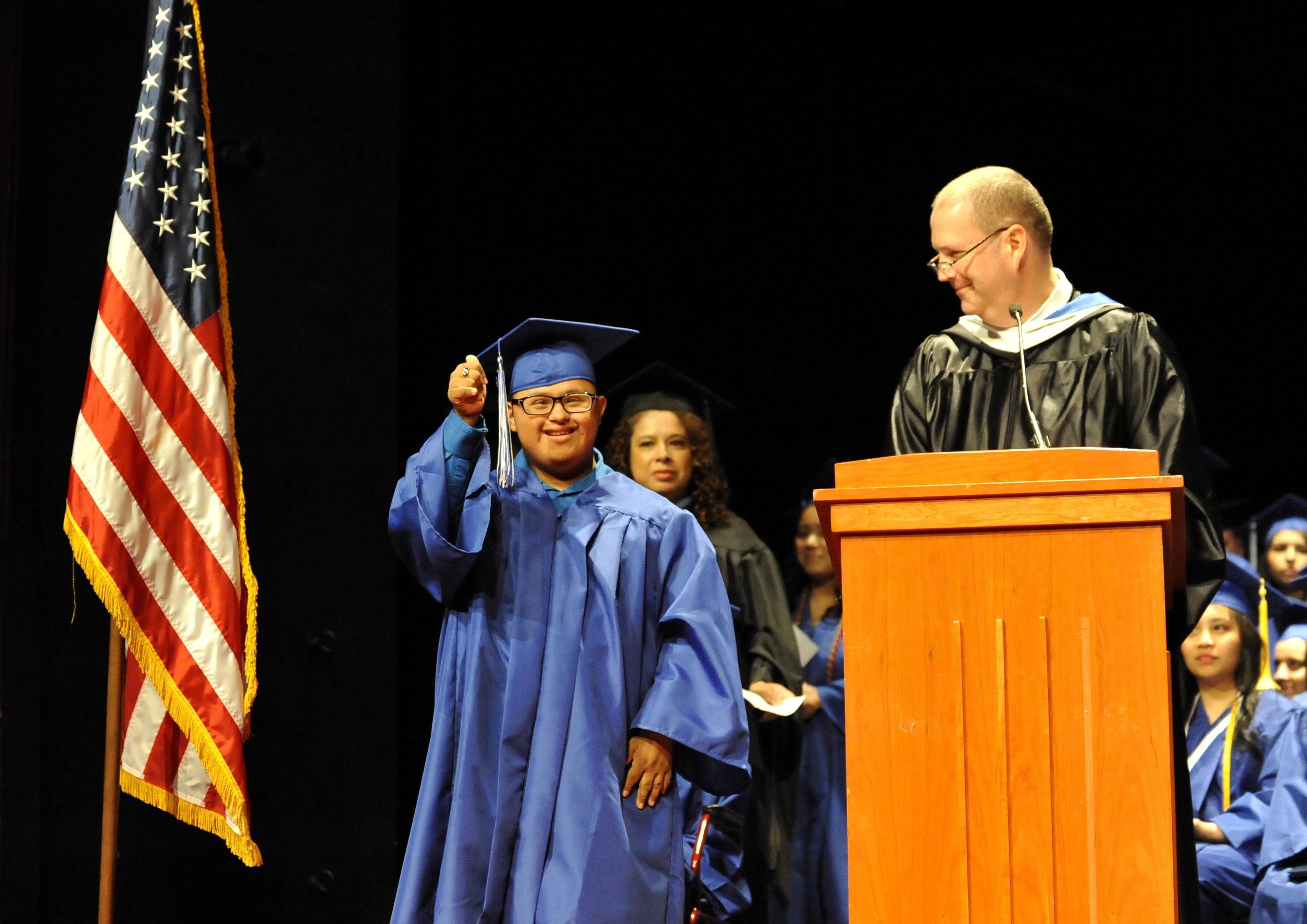 Alfonso Mercado cheers as he receives his diploma.