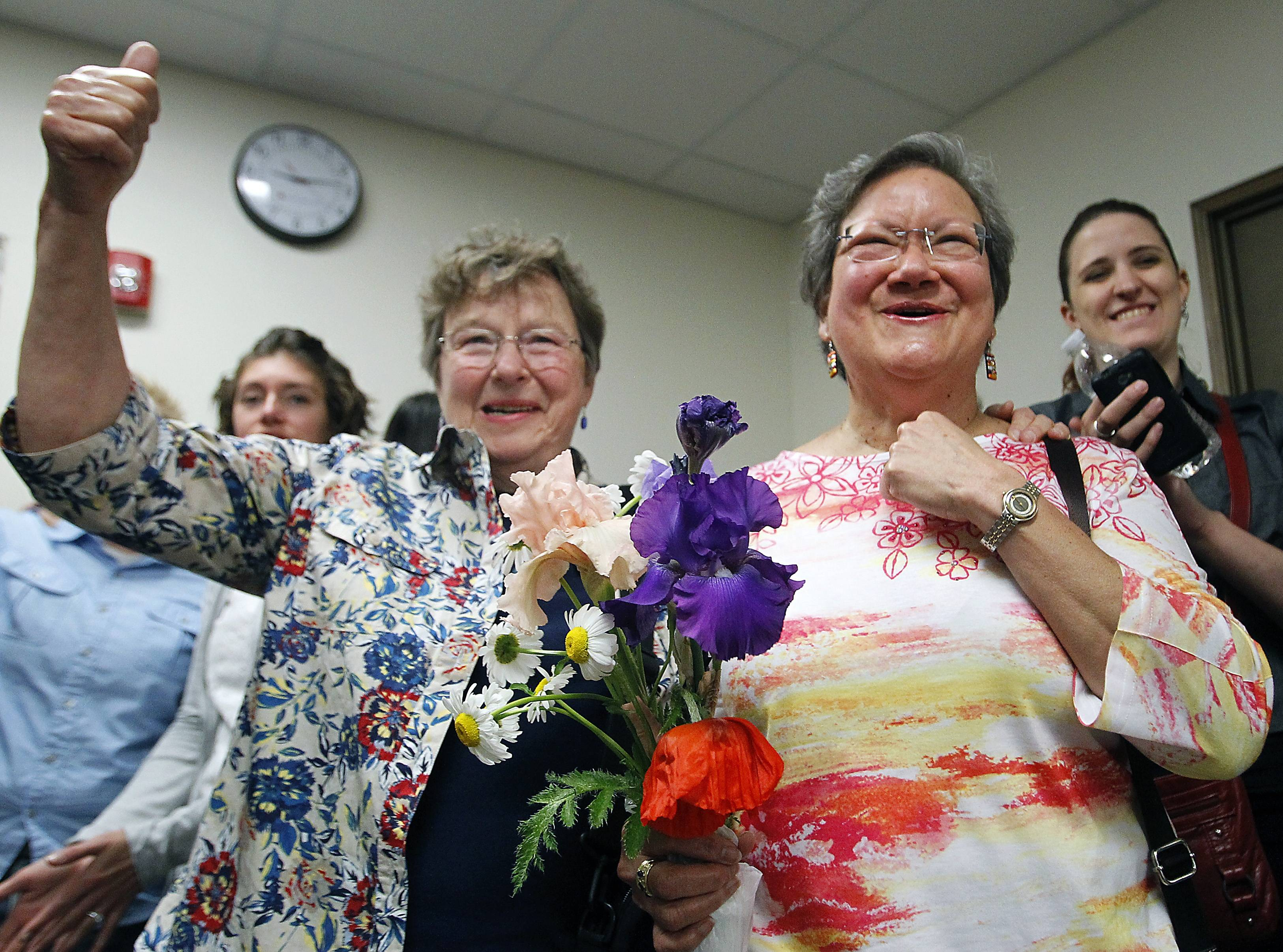Miriam Douglass, left, and Ligia Rivera react to Monday's announcement that marriage licenses would be granted, subject to a five-day waiting period, in Outagamie County, Wis. The two were given the first same-sex marriage license in the county.