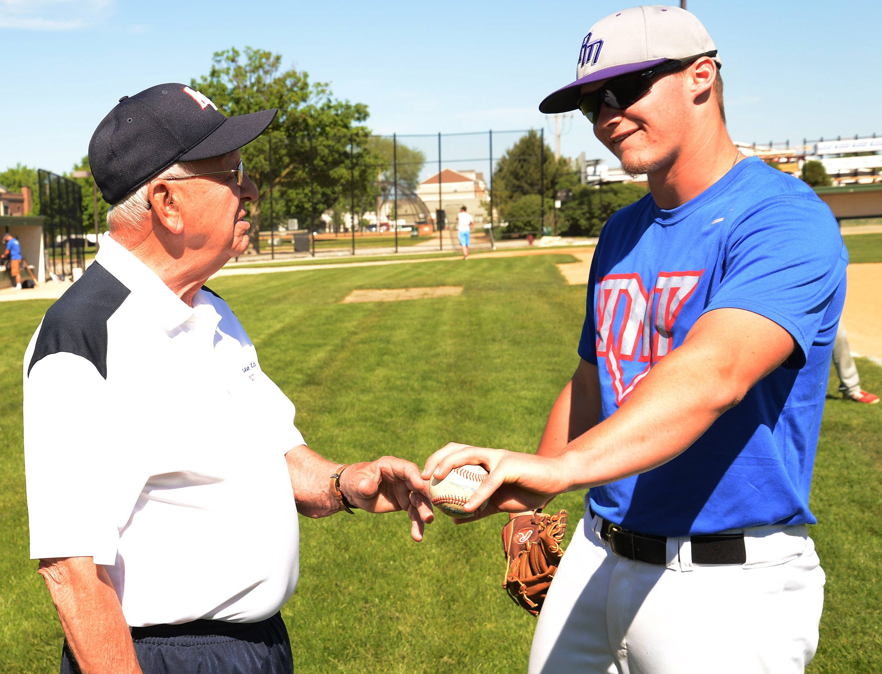 Lloyd Meyer, who is starting his 61st year of coaching American Legion baseball, works with pitcher Erik Schurtz of Arlington Heights.