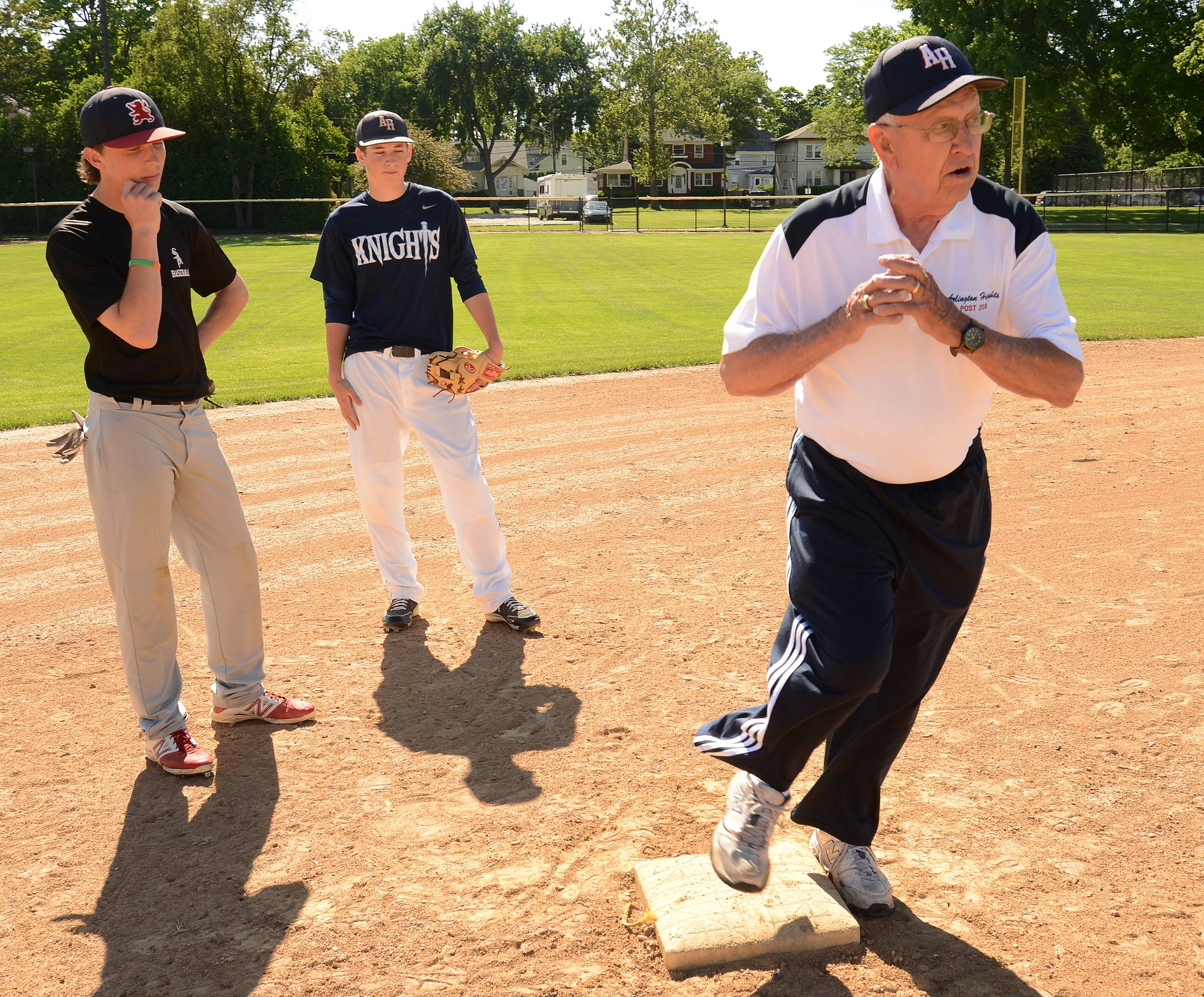 Lloyd Meyer, who is starting his 61st year of coaching American Legion baseball, shows Matt Darling, left, and Grant Gerdes how to turn a double play.