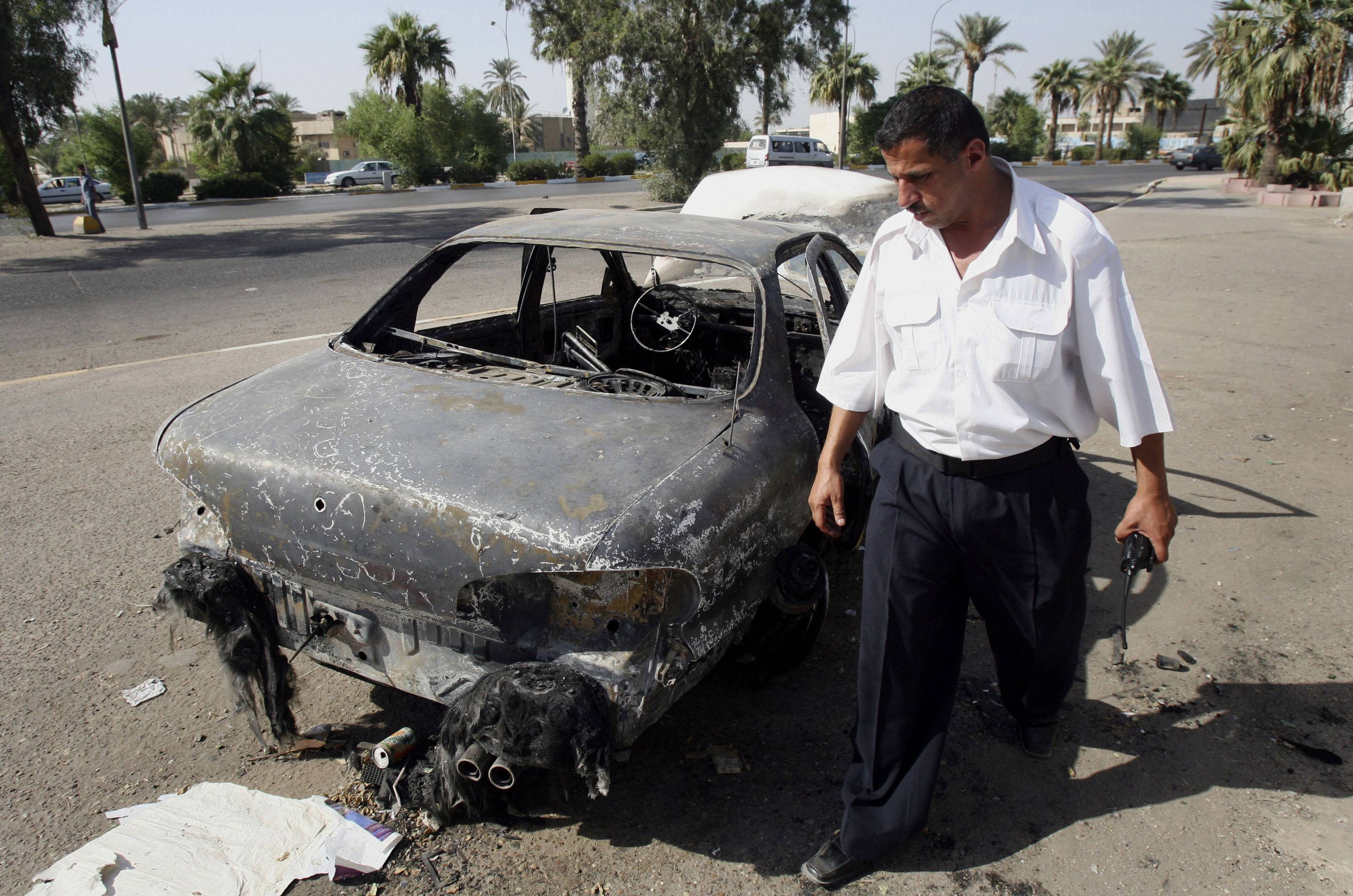This Sept. 25, 2007 file photo shows an Iraqi traffic policeman inspects a car destroyed by a Blackwater security detail in al-Nisoor Square in Baghdad, Iraq. After years of delays, four former guards from the security firm Blackwater Worldwide are facing trial in the killings of 14 Iraqi civilians and the wounding of 18 others in bloodshed that inflamed anti-American sentiment around the globe. Whether the shootings were self-defense or an unprovoked attack, the carnage of Sept. 16, 2007 was seen by critics of the George W. Bush administration as an illustration of a war gone horribly wrong. A trial in the nearly 7-year-old case is scheduled to begin wi