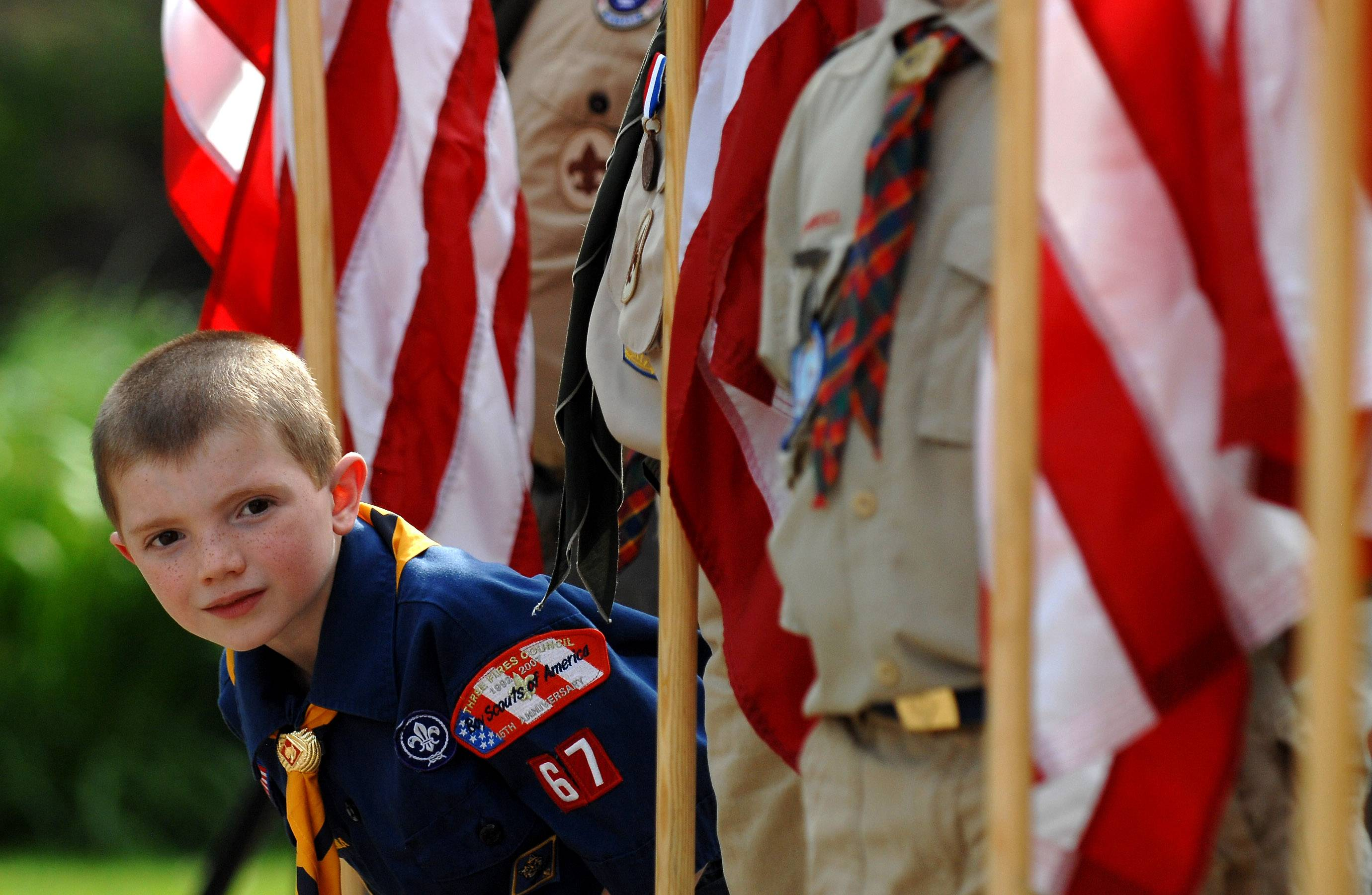 Cub Scout Keegan Carver, 7, of Elgin Pack 67, peeks out at the row of flags during a previous Elgin Flag Day ceremony.