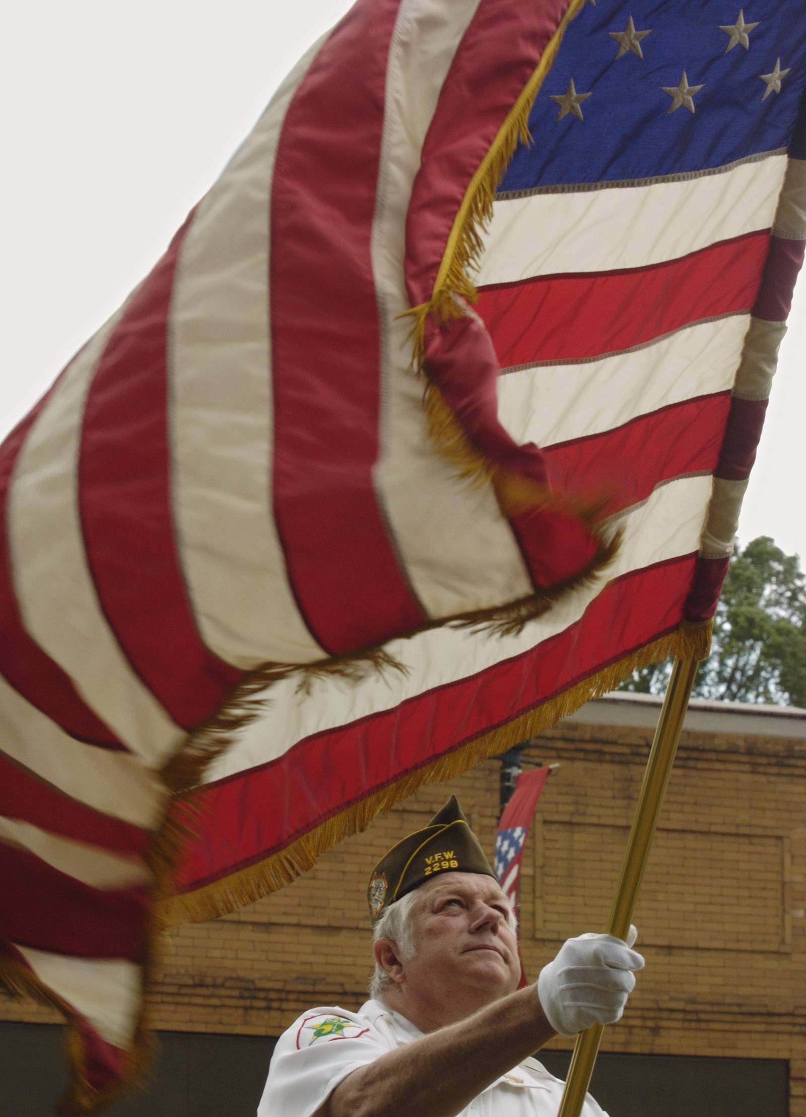 Larry Fettes of Veterans of Foreign Wars Post 2298 in West Dundee, holds a billowing American flag during a previous Flag Day ceremony in East Dundee.