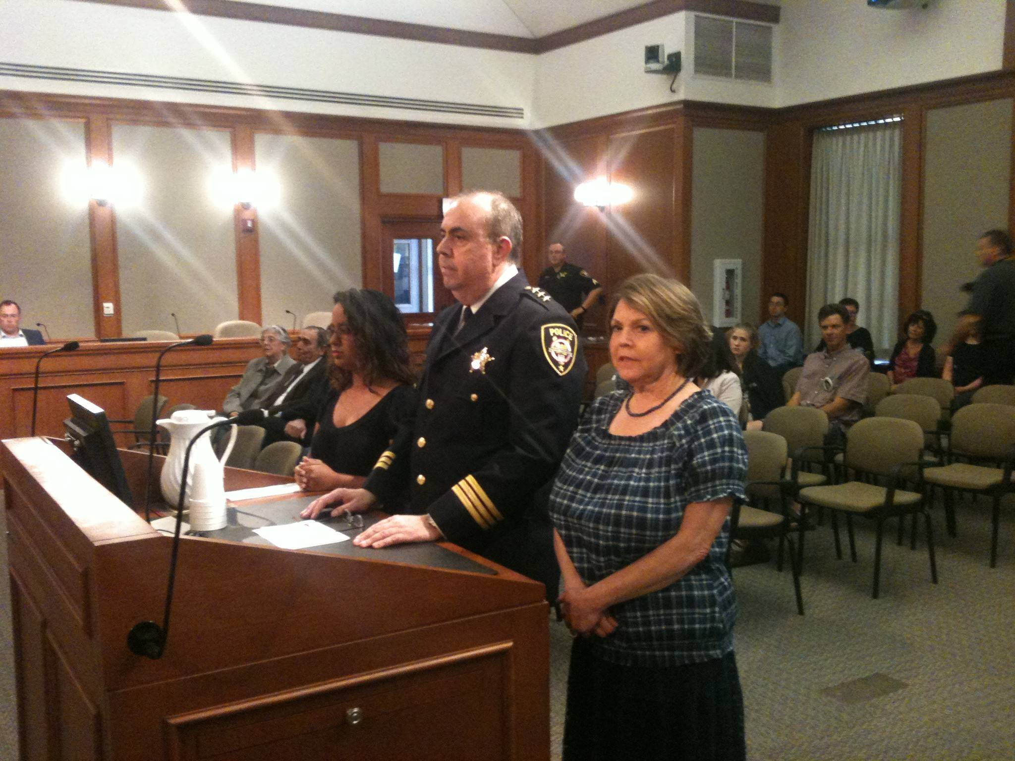 Retiring Mount Prospect Police Chief Michael Semkiu is honored at the MP village board on June 3, 2014 flanked by his wife Rosann and his daughter, Rebecca.
