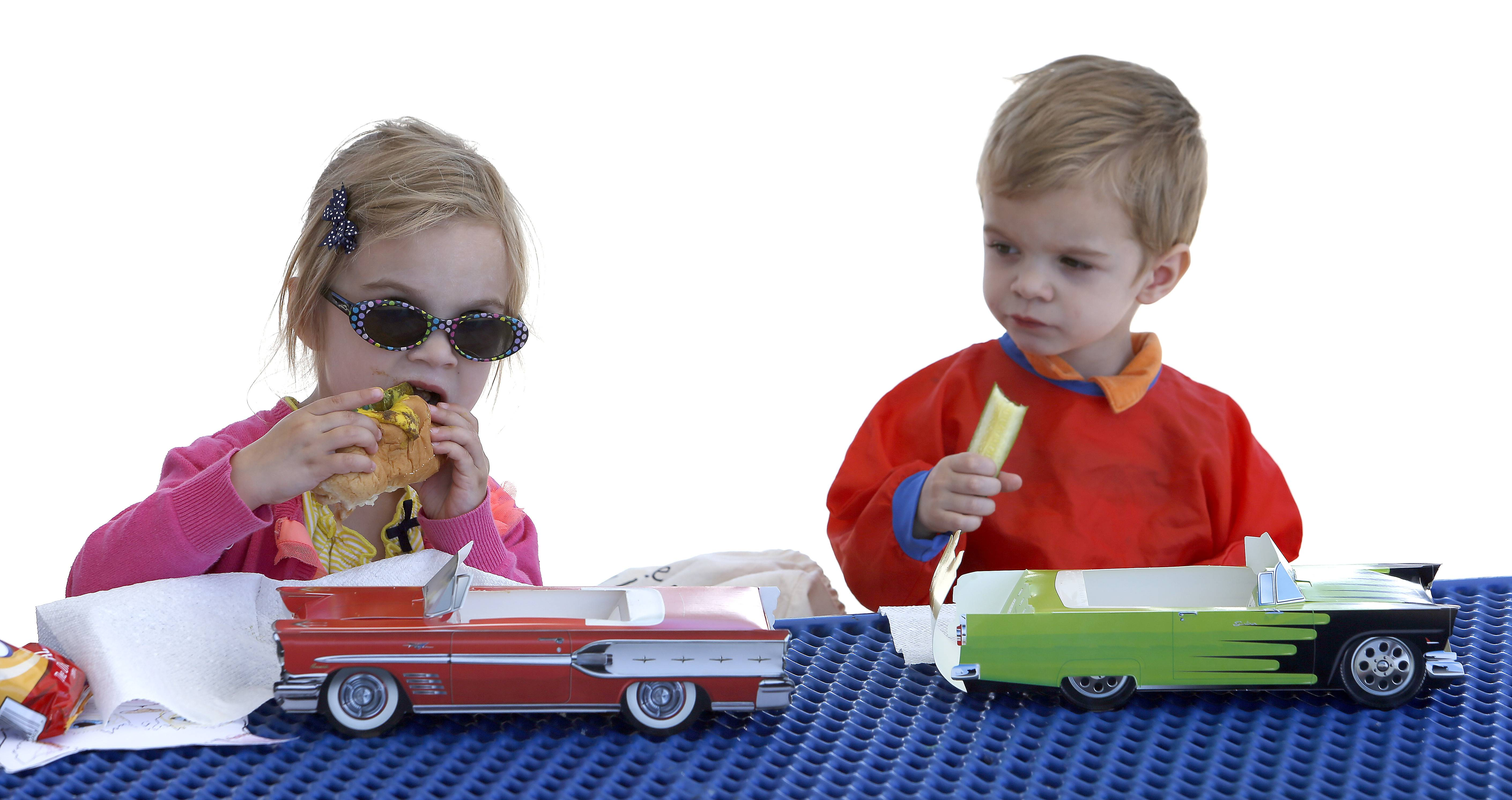 Nora Newby, 4, and her younger brother Nelson, 2, both of Elgin, enjoy a hot dog with all the fixings during the first day of the Elgin Harvest Market. The hot dogs came in a cardboard box shaped like a classic car. The Downtown Neighborhood Association of Elgin's Harvest Market will run 9 a.m. to 2 p.m. every Thursday through Oct. 2, at 200 N. Grove, across from the Gail Borden Public Library in downtown Elgin. For more information about the 2014 Downtown Elgin Harvest Market season, contact market manager Jennifer Benson at (847) 488-1456 or visit elginharvestmarket.com.