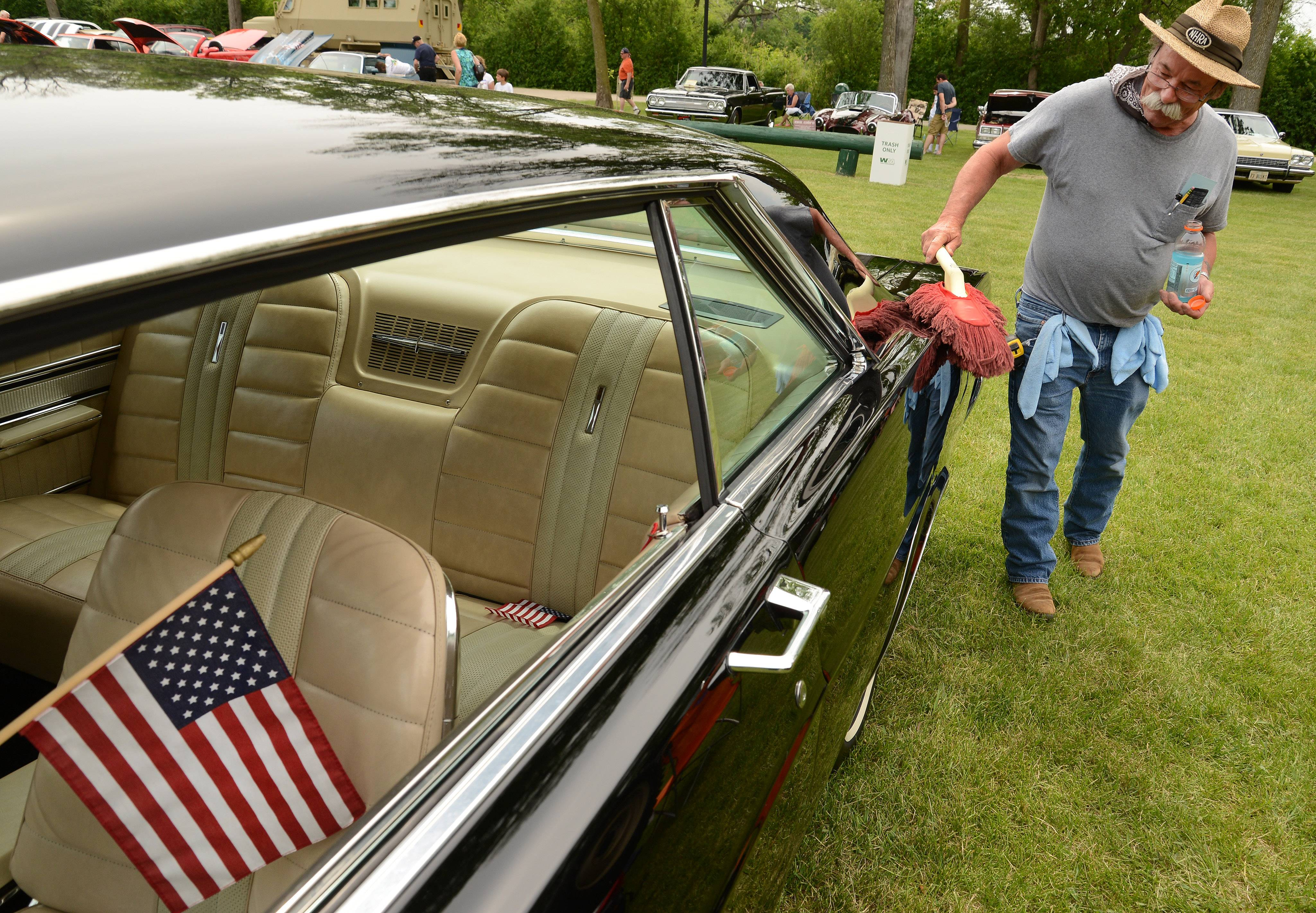 Bill Foley, of Richmond, dusts off his 1966 7-liter Ford Galaxie at the Lake Villa Celebration of Summer Saturday in Lehmann Park.