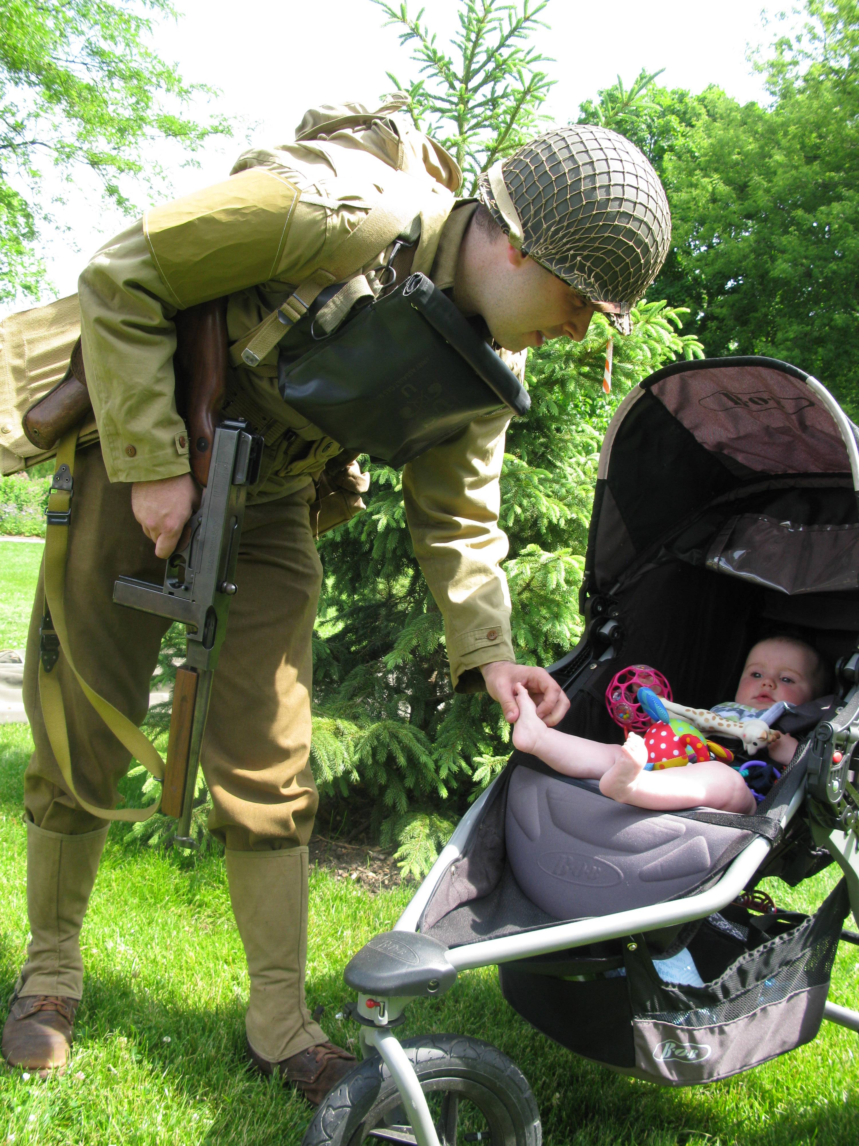 Aaron Conklin, 31, of Plainfield, with the Living History Detachment of the First Division Museum at Cantigny Park, takes a break to watch his 8-month-old daughter, Carla. Conklin is dressed as a World War II 1st Infantry Division soldier demonstrating what first wave troops wore when they landed on the beaches of Normandy, France, on D-Day.