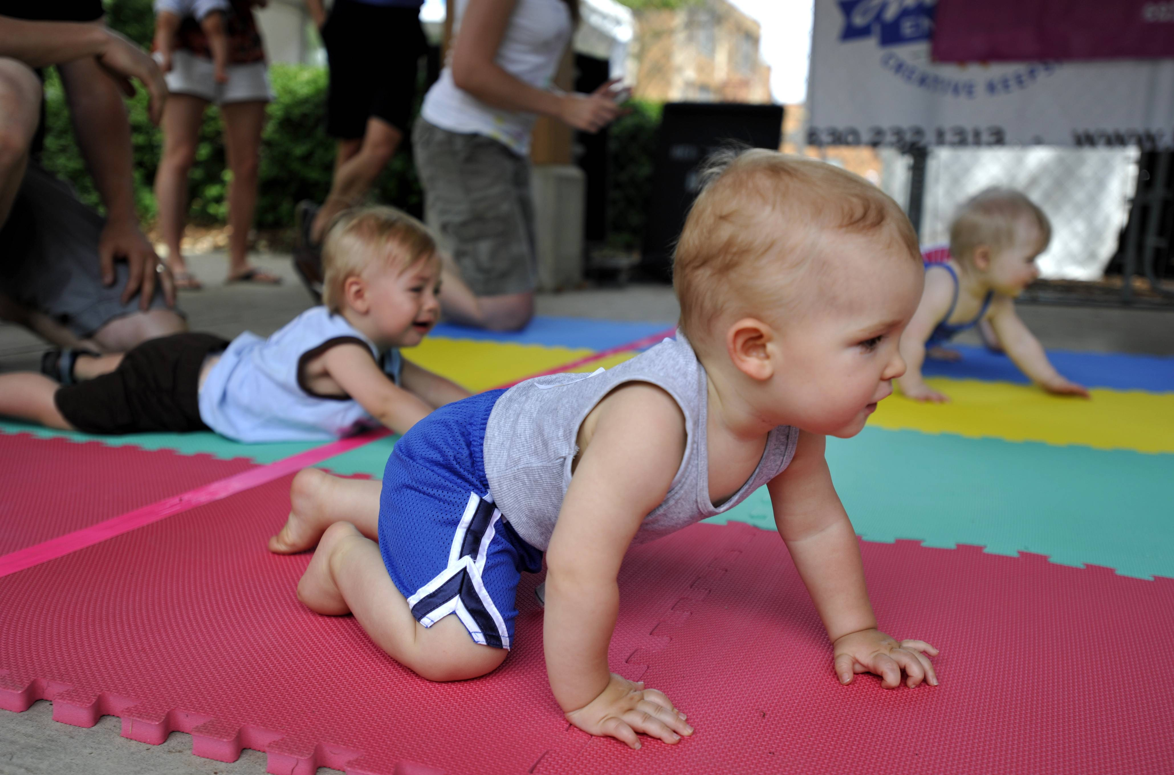 "Liam Granquist, 11 months, of South Elgin, front, Brady Tolkson, 13 months, of St. Charles, far left, and Sienna Stoll, 11 months, of Carpentersville, back, face off in the St. Charles Mothers' Club Diaper Dash in Lincoln Park during the City of St. Charles RiverFest on Saturday. Despite his tears and slow start, Brady finished in first place. His mother Karlen Tolkson said it was their first time doing the diaper dash, ""it just sounded so funny, so I signed up."""