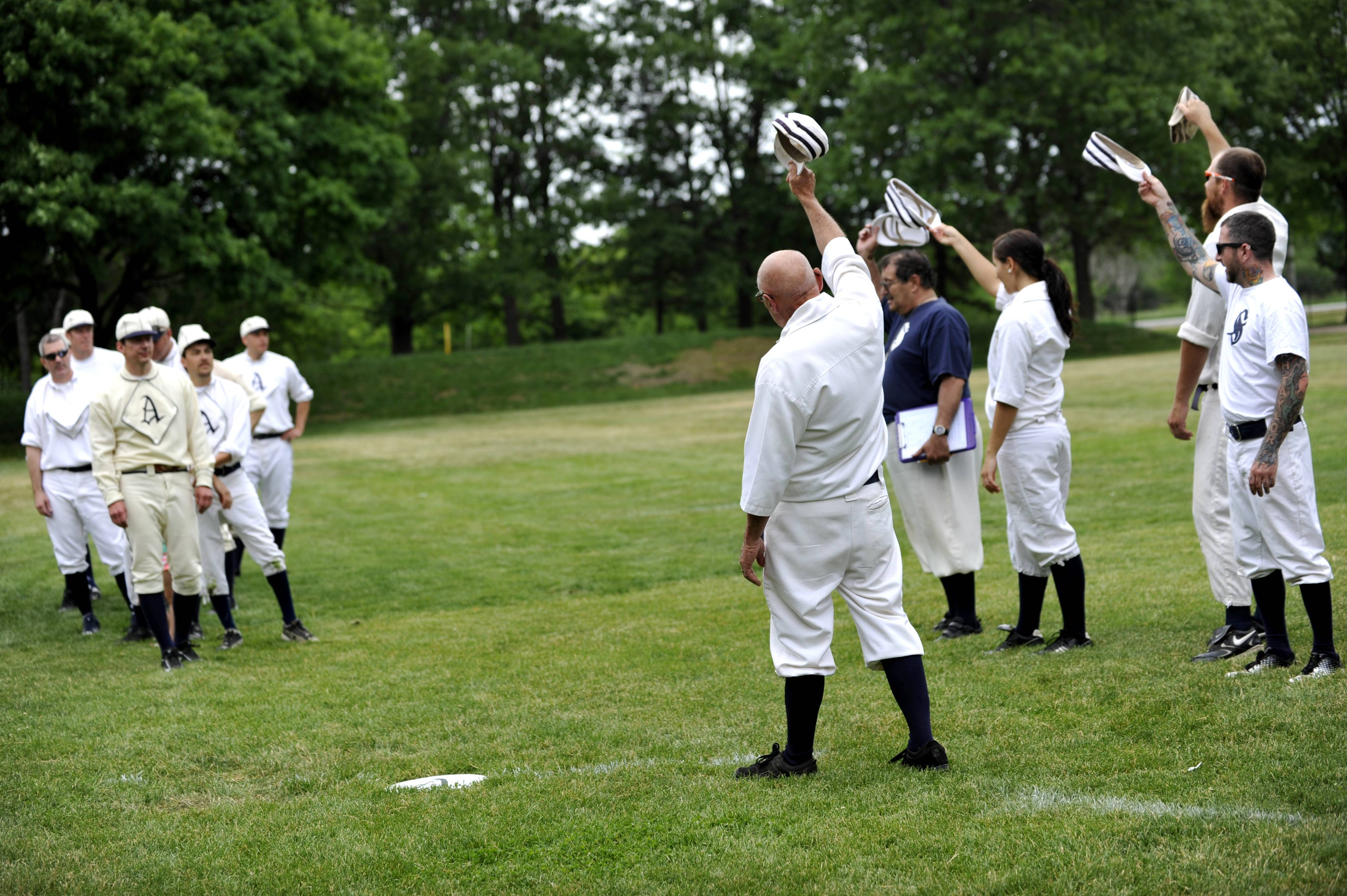 "The Somonauk Blue Stockings vintage baseball league salute their friendly rivals the Aurora Town Club with the traditional ""Hip Hip Hooray!"" at a vintage baseball game at Blackberry Farm in Aurora on Saturday. Mike Adrian of Somonauk, center, started the Blue Stockings, a vintage baseball league nine years ago and this was the third game of the season."