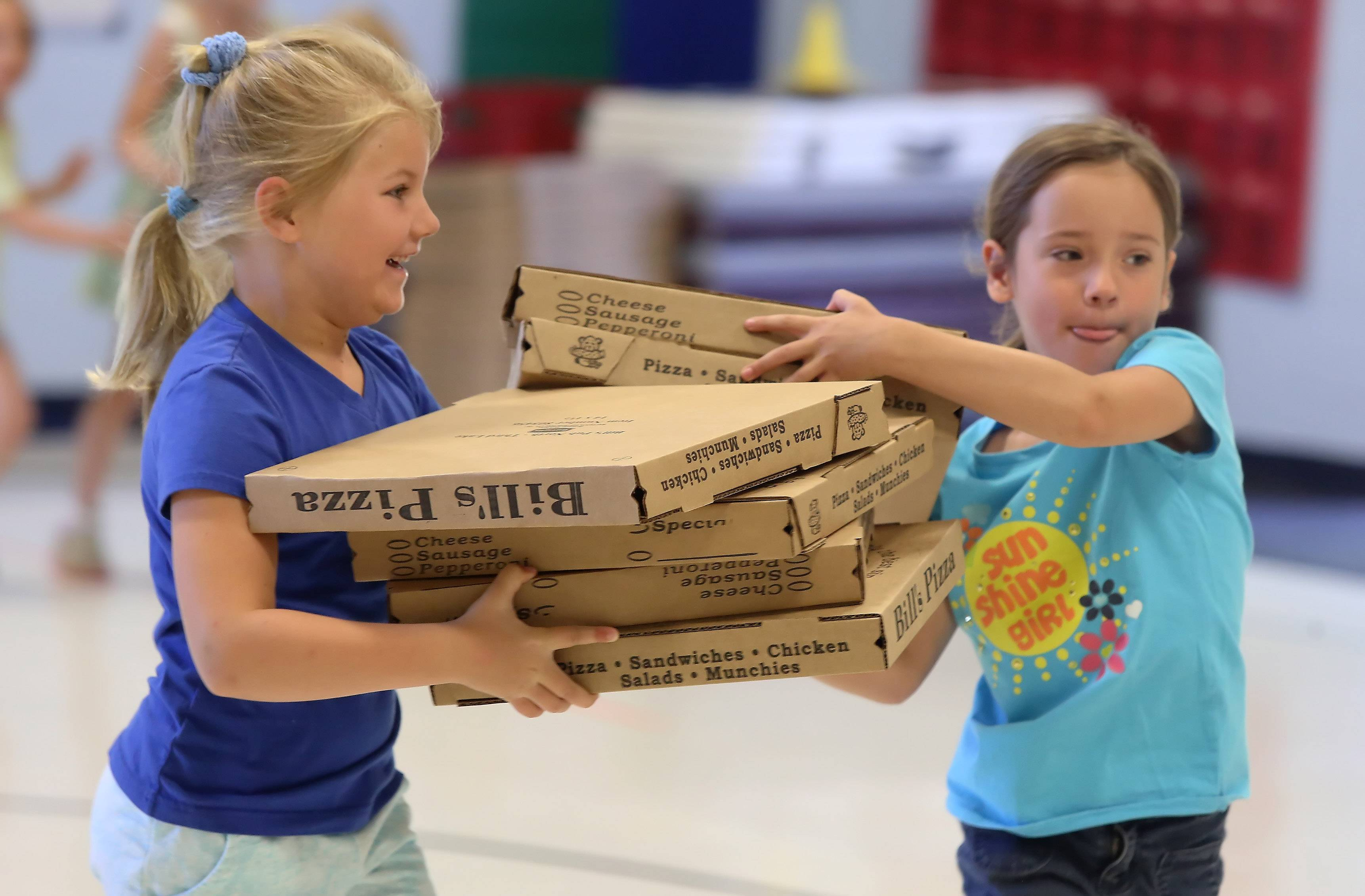 Kindergartners Jessica Sadowska, left, and Annie Lock, compete in the pizza box relays during Field Day on Tuesday at Adler Park School in Libertyville. There were more than 50 parent volunteers to help out with games like potato hockey relays, pizza box relays and the three-legged race.