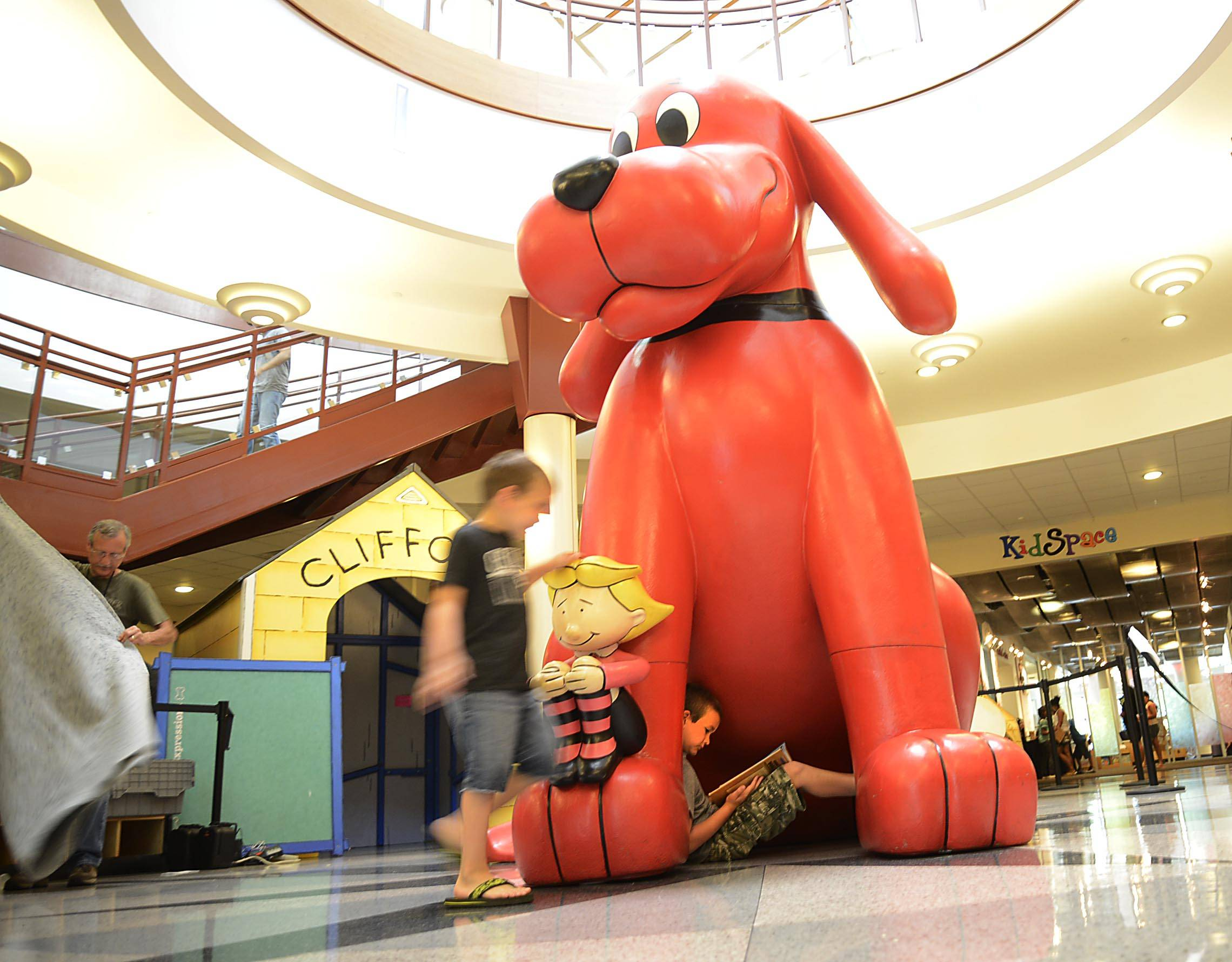 Trevor Willis, 7, sits under a nine-foot Clifford The Big Red Dog exhibit at the Gail Borden Public Library Tuesday in Elgin, as his brother Jonathan explores the site. The Elgin boys were with their mother Clara. The 10-site, interactive exhibit is part of the summer reading program called Paws to Read.