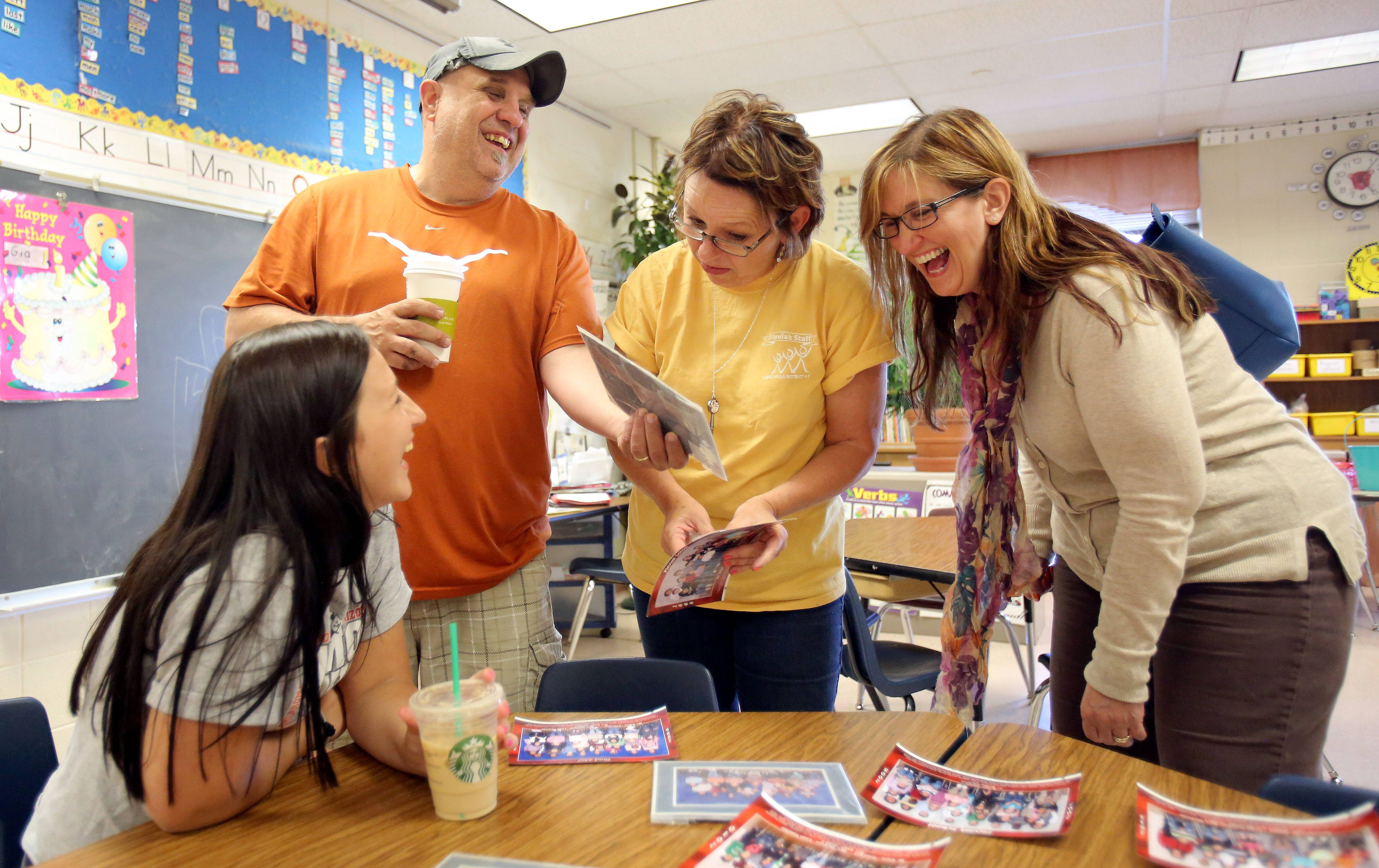 From left, Sami Sandeki, Dennis Sandeki, teacher Linda Smart, and Cheryl Sandeki, look through old class pictures during an open house at Pleviak School in Lake Villa Tuesday. Alumns got a chance to say goodbye to the school as it is transitioned into an all kindergarten school.