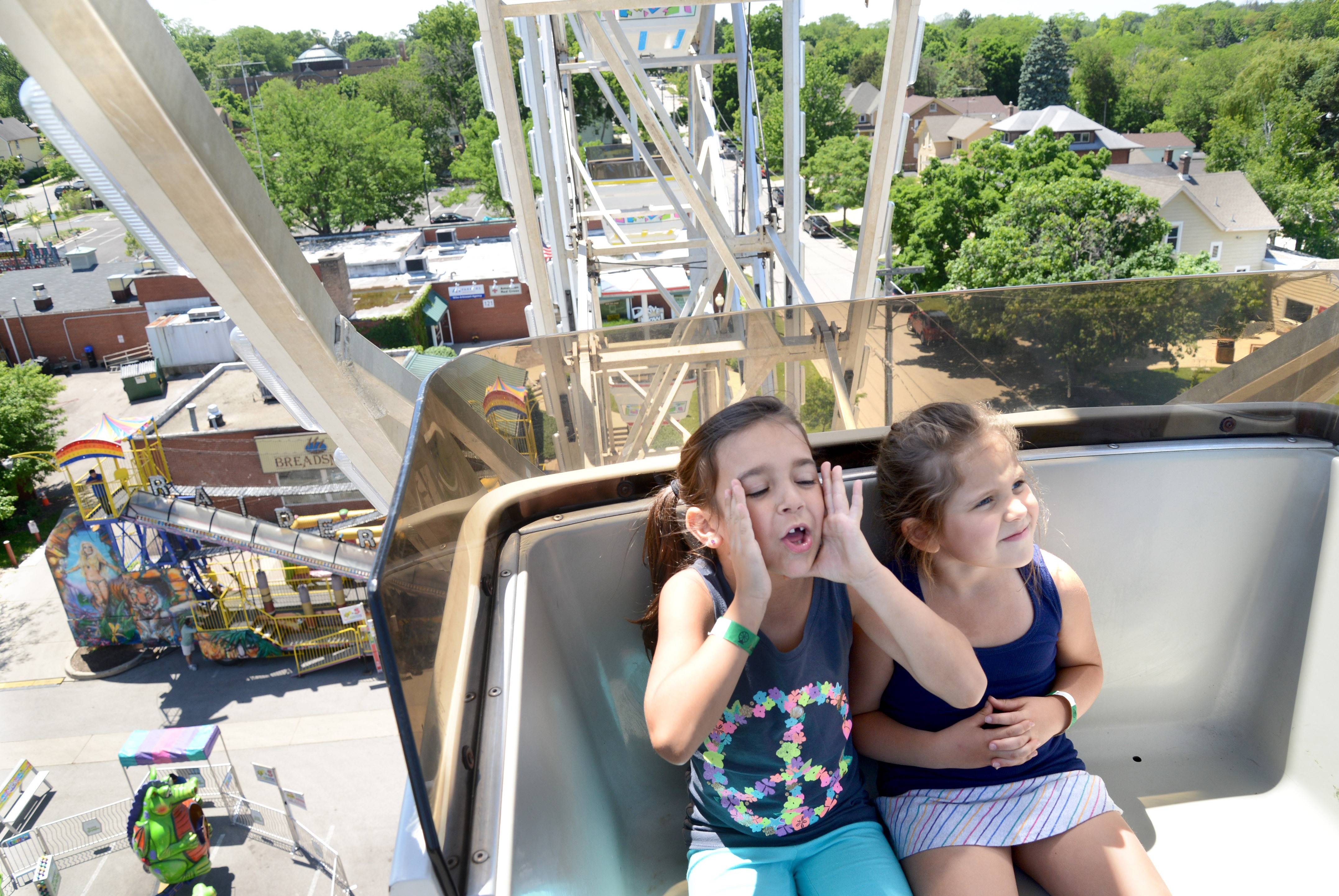 "Ava Skwierawski, 6, of South Elgin, lets out a ""whoo hoo!"" from the top of the ferris wheel during the first day of the carnival in downtown St. Charles on Thursday. Her friend, Gabriella Tayfel, 5, of Bloomingdale, wasn't feeling the same excitement for the ride. Roller coasters are more her style. The carnival opening kicked off the start of the town's RiverFest weekend, and the girls took advantage of the unlimited rides $25 wristband special from 1-5pm."