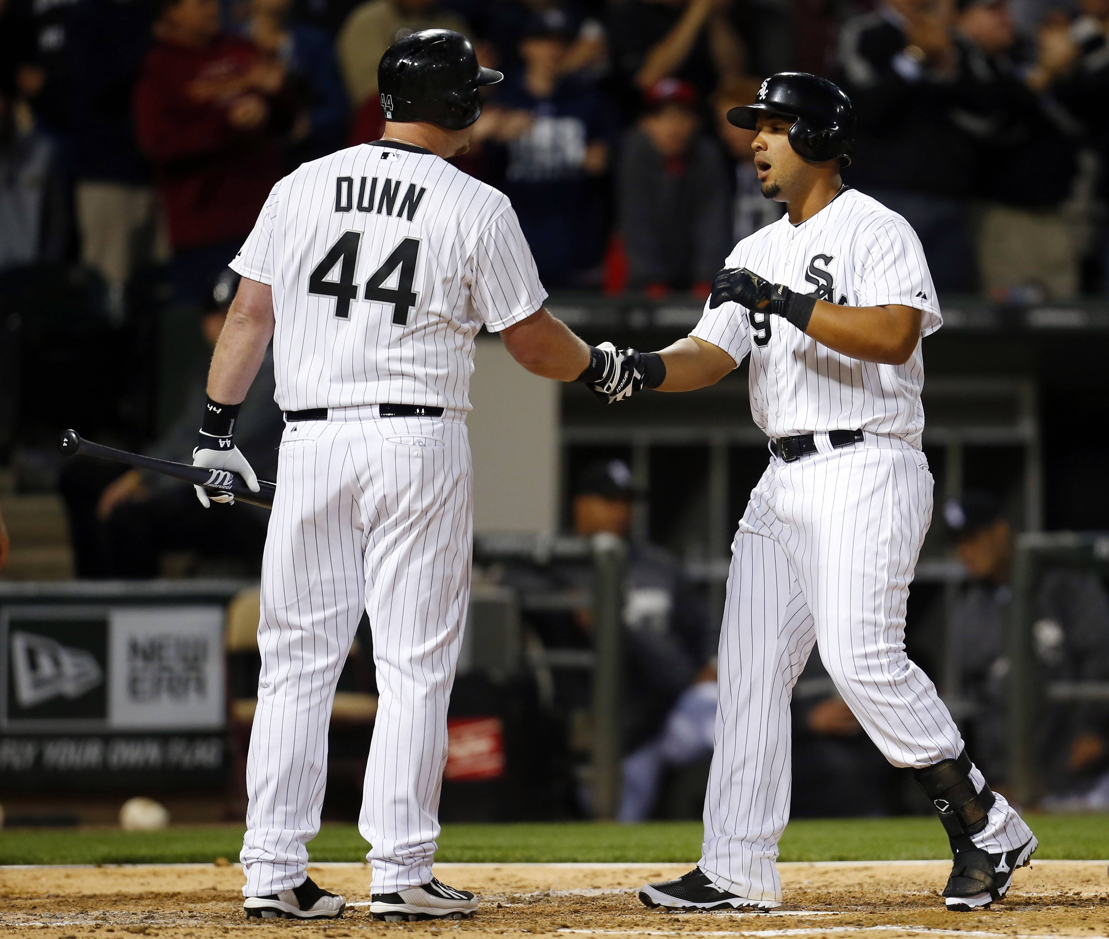 White Sox first baseman Jose Abreu is greeted by Adam Dunn at home plate after hitting a 2-run homer against the Tigers in the fifth inning Monday night.