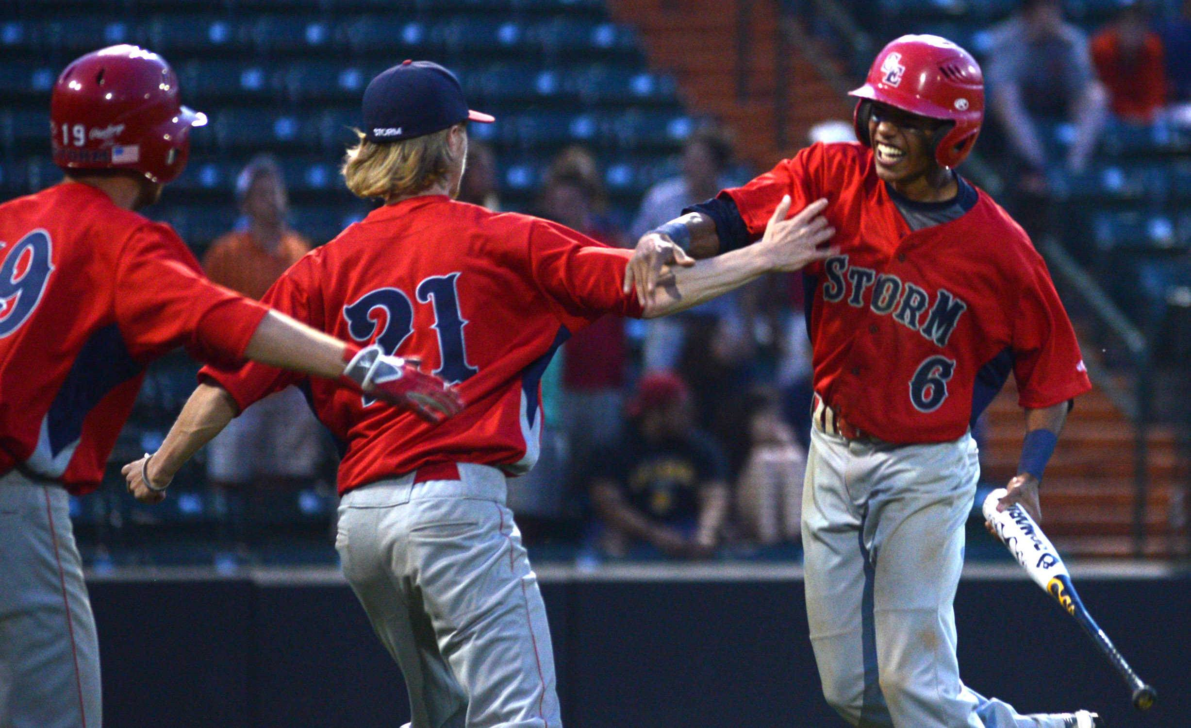 South Elgin's Justin Howard, right, is greeted by Craig Kelly, center, and Jared Kramer, left, after Howard scored during the Class 4A supersectional baseball game against Evanston at Boomers Stadium in Schaumburg on Monday night.
