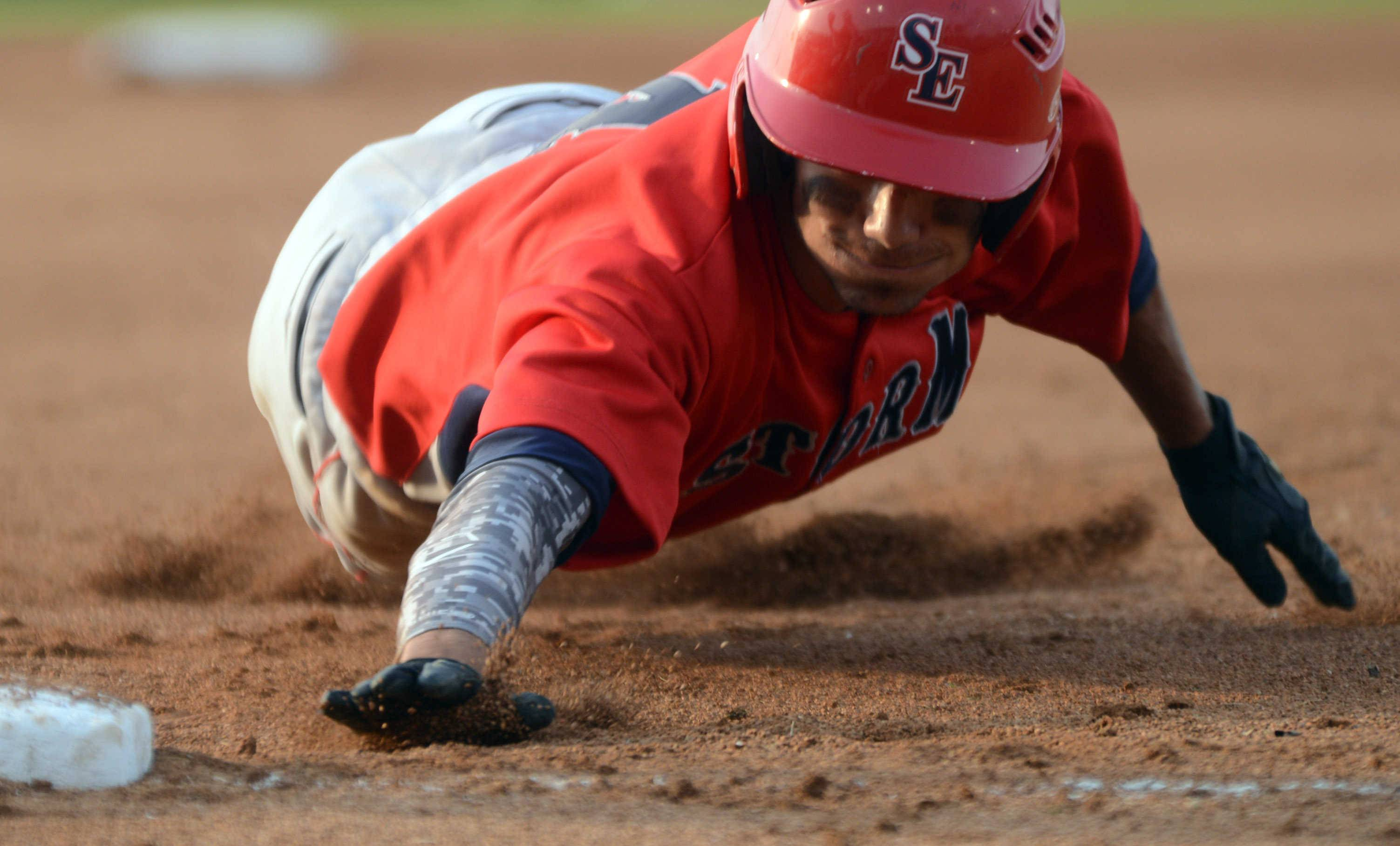 South Elgin's Dane Toppel dives back to first base safely during the Class 4A supersectional baseball game at Boomers Stadium in Schaumburg on Monday night. The Storm won 7-6.