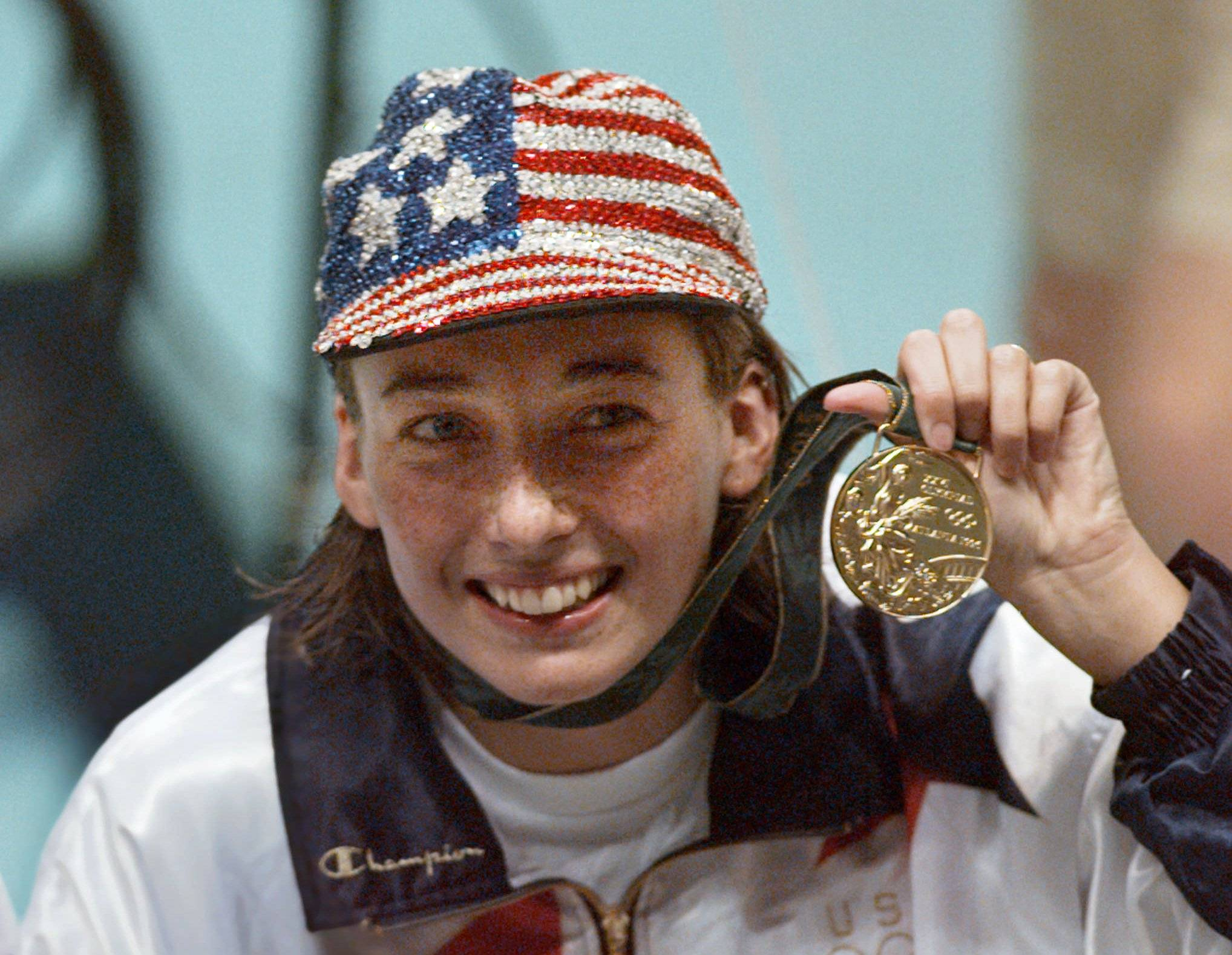 Amy Van Dyken holds her gold medal after winning the women's 50 meter freestyle at the 1996 Summer Olympic Games in Atlanta.