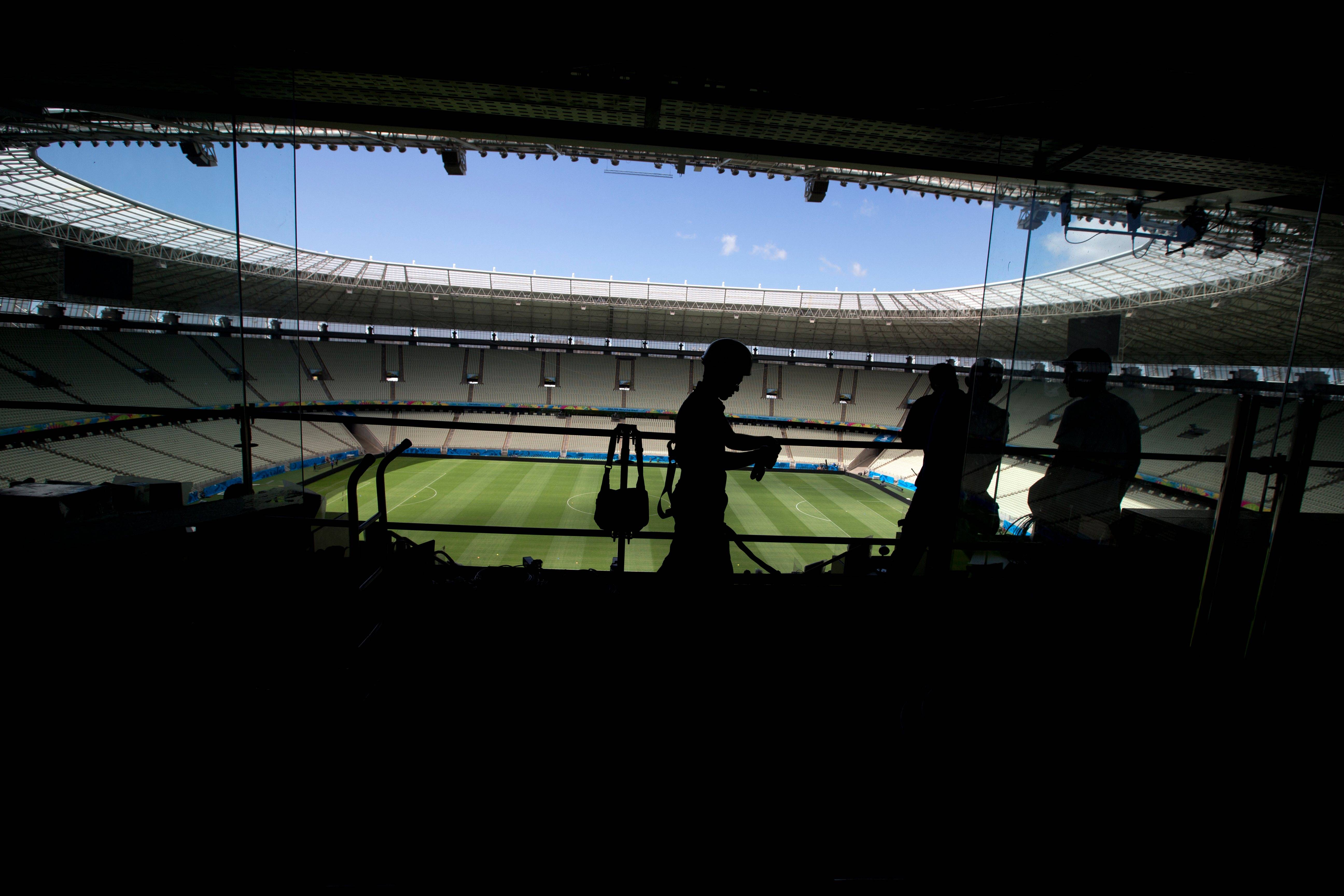 Workers put the final touches in the press box Monday at the Arena Castelão in Fortaleza, Brazil. The Brazil 2014 World Cup soccer tournament is set to begin in just a few days.