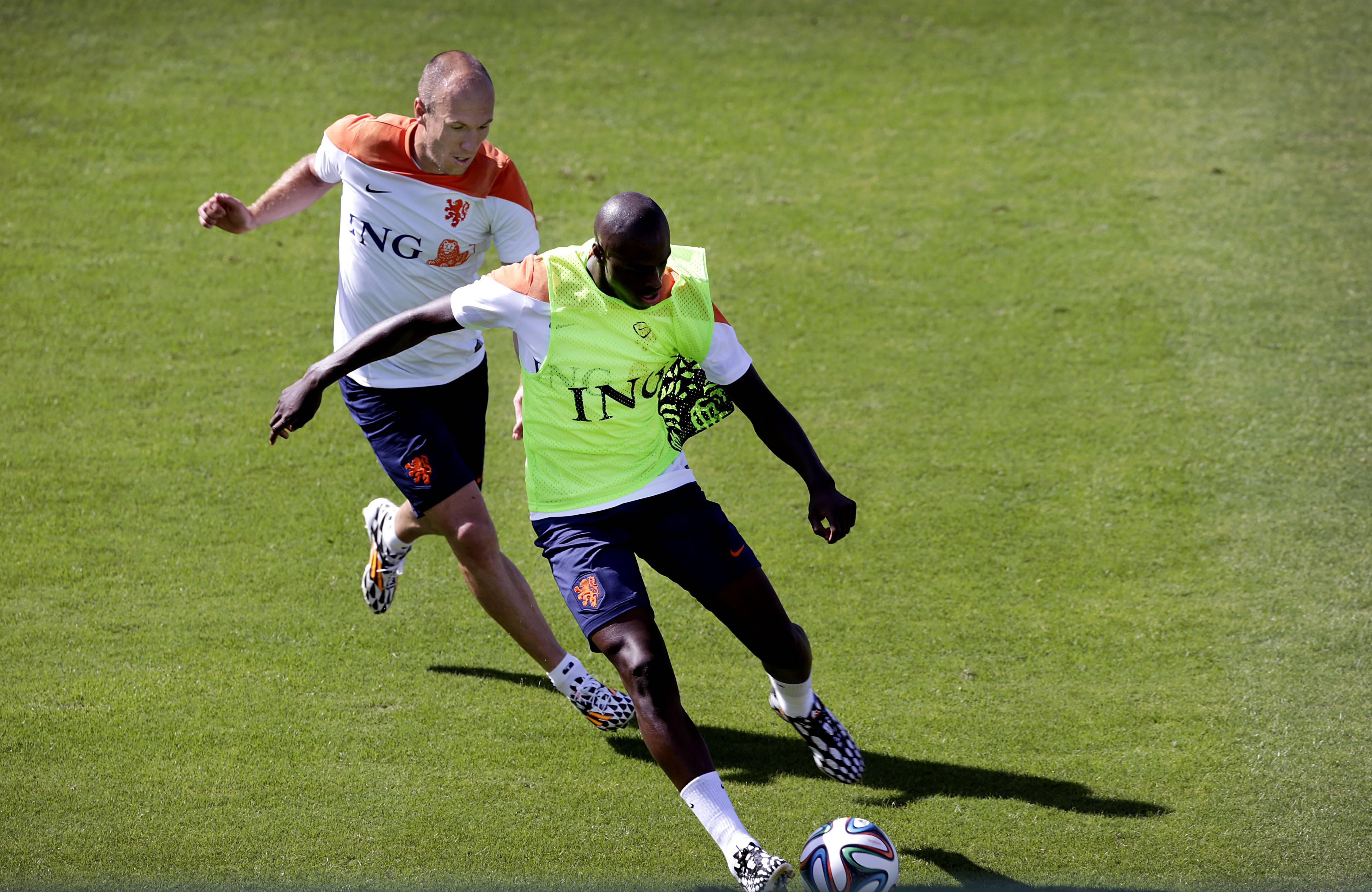 Arjen Robben, left, and Bruno Martins Indi from the Netherlands soccer team run after the ball during a training session Sunday in Rio de Janeiro, Brazil. There is no love lost between the two players.