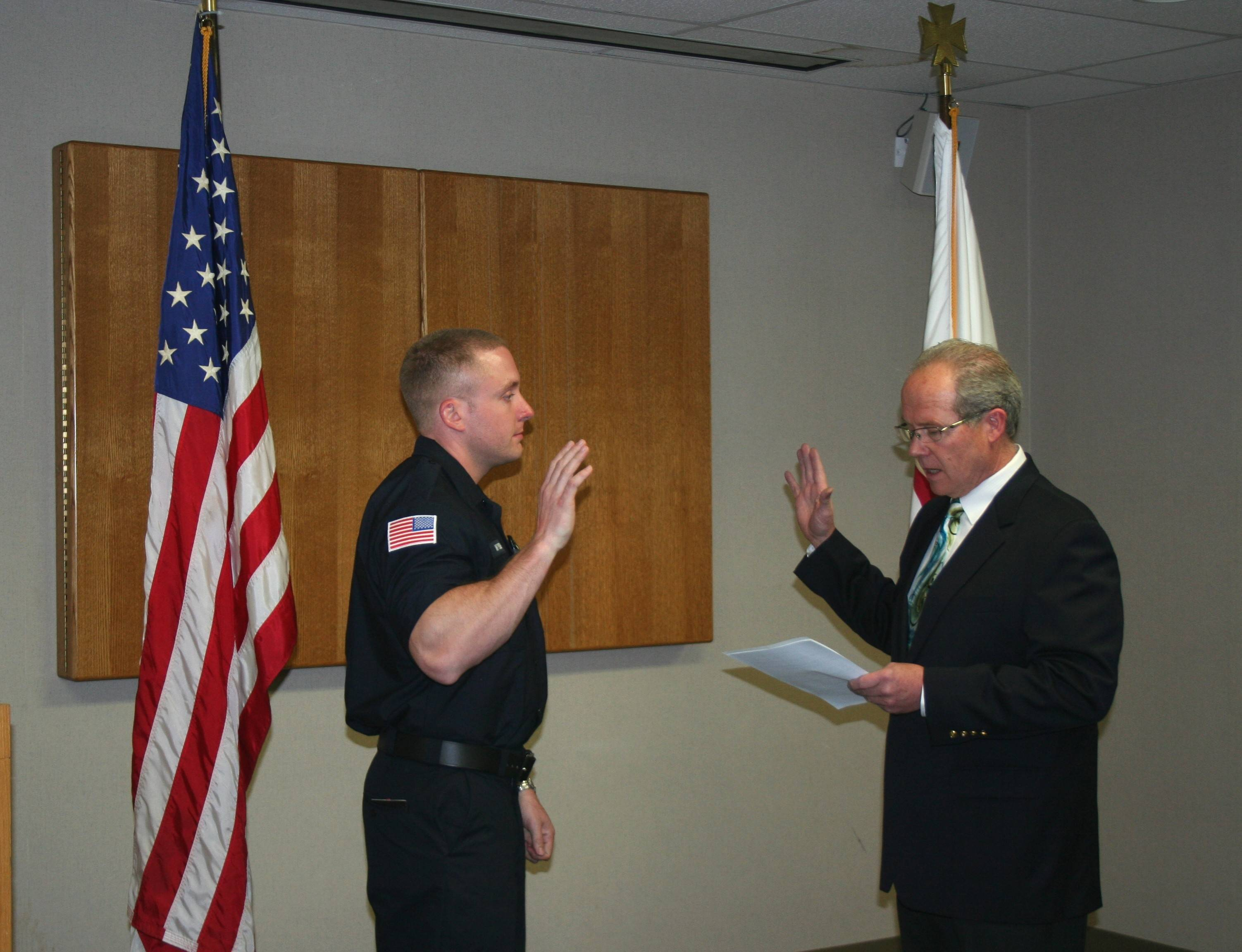 Board of Fire and Police Commissioner Mark Busse, right, administers the oath of office to Joseph Wysong, who joined the Mount Prospect Fire Department as a firefighter/paramedic on June 2.