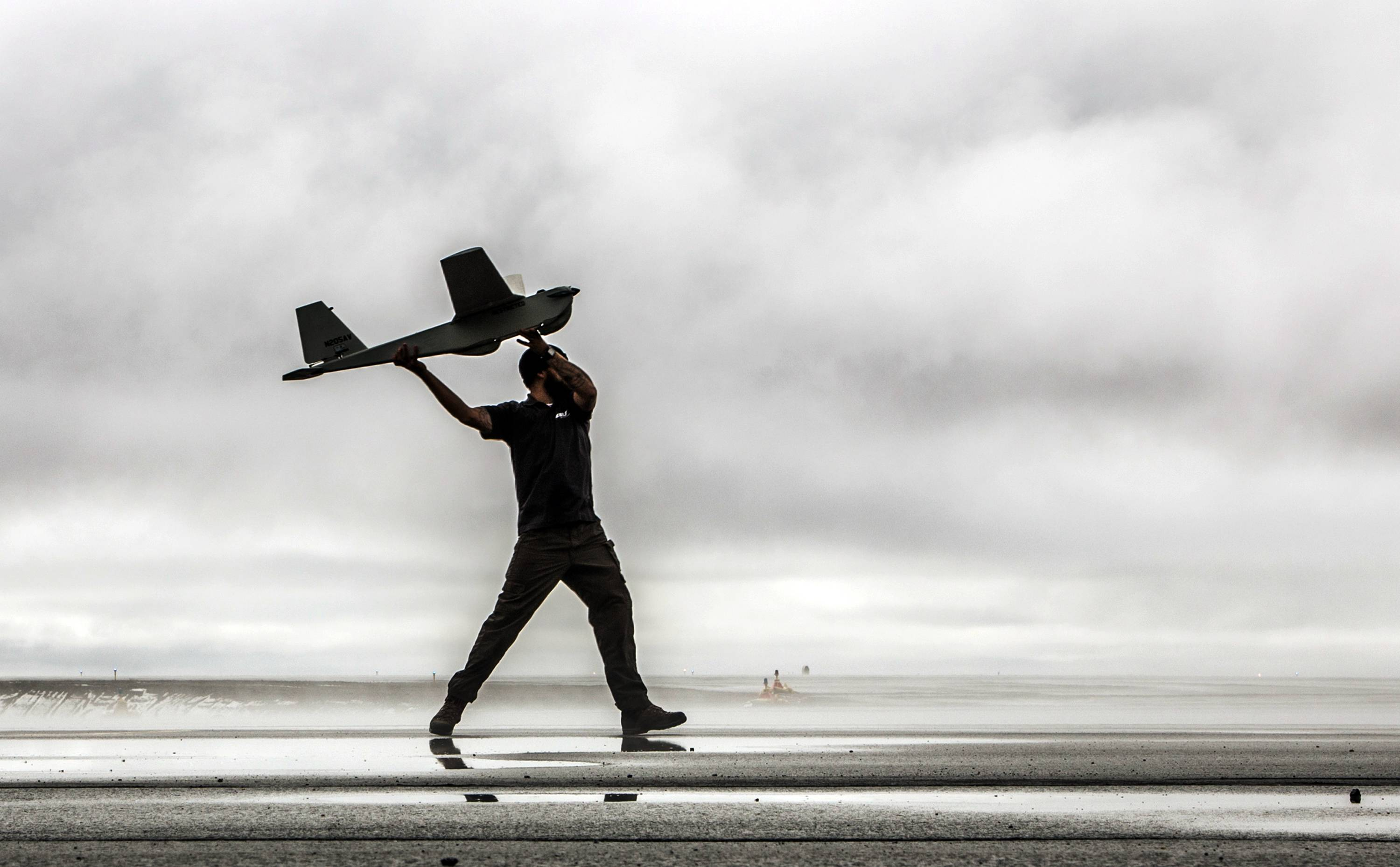 A man hand-launches a Puma drone aricraft. The Federal Aviation Administration said Tuesday it has granted the first permission for commercial drone flights over land.