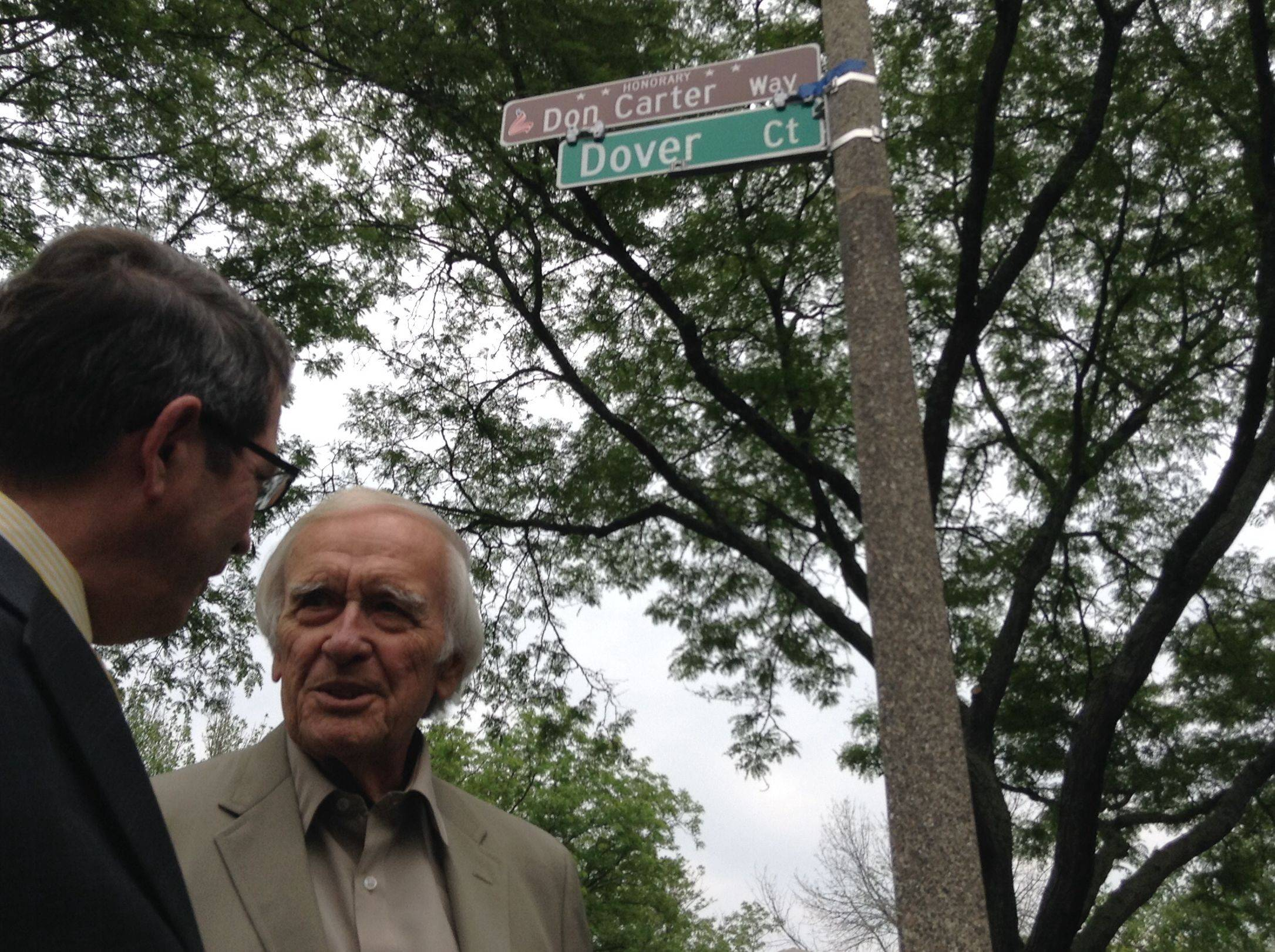 Libertyville Mayor Terry Weppler, left, unveiled the village's first honorary street sign for World War II veteran and longtime resident Don Carter, right.