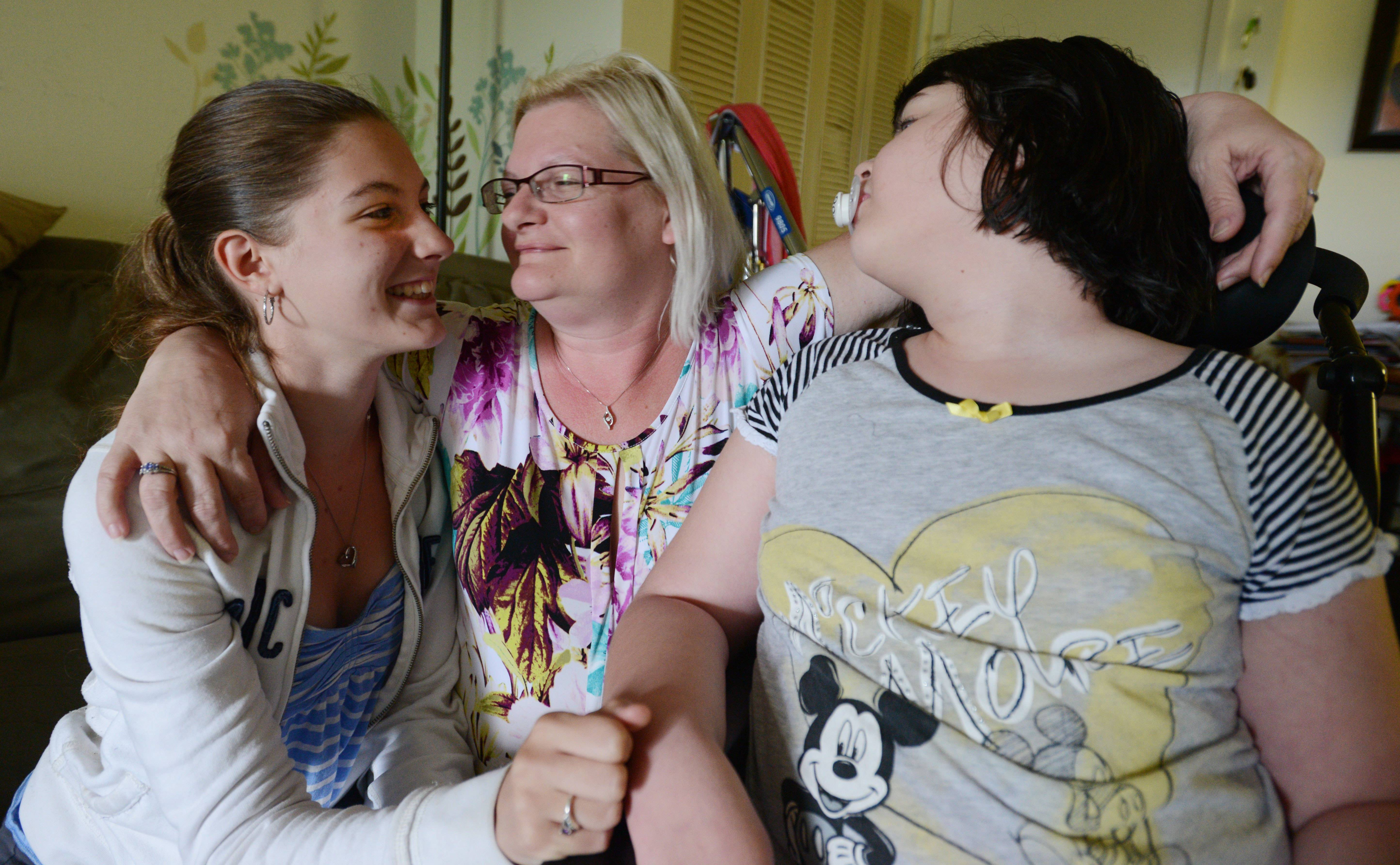 While willing to talk about the tough times that led her to a food pantry, mom and new college graduate Ellen Tucker shares a happy moment with daughters Sydney, 14, and Emma, 11, who has life-threatening disabilities.