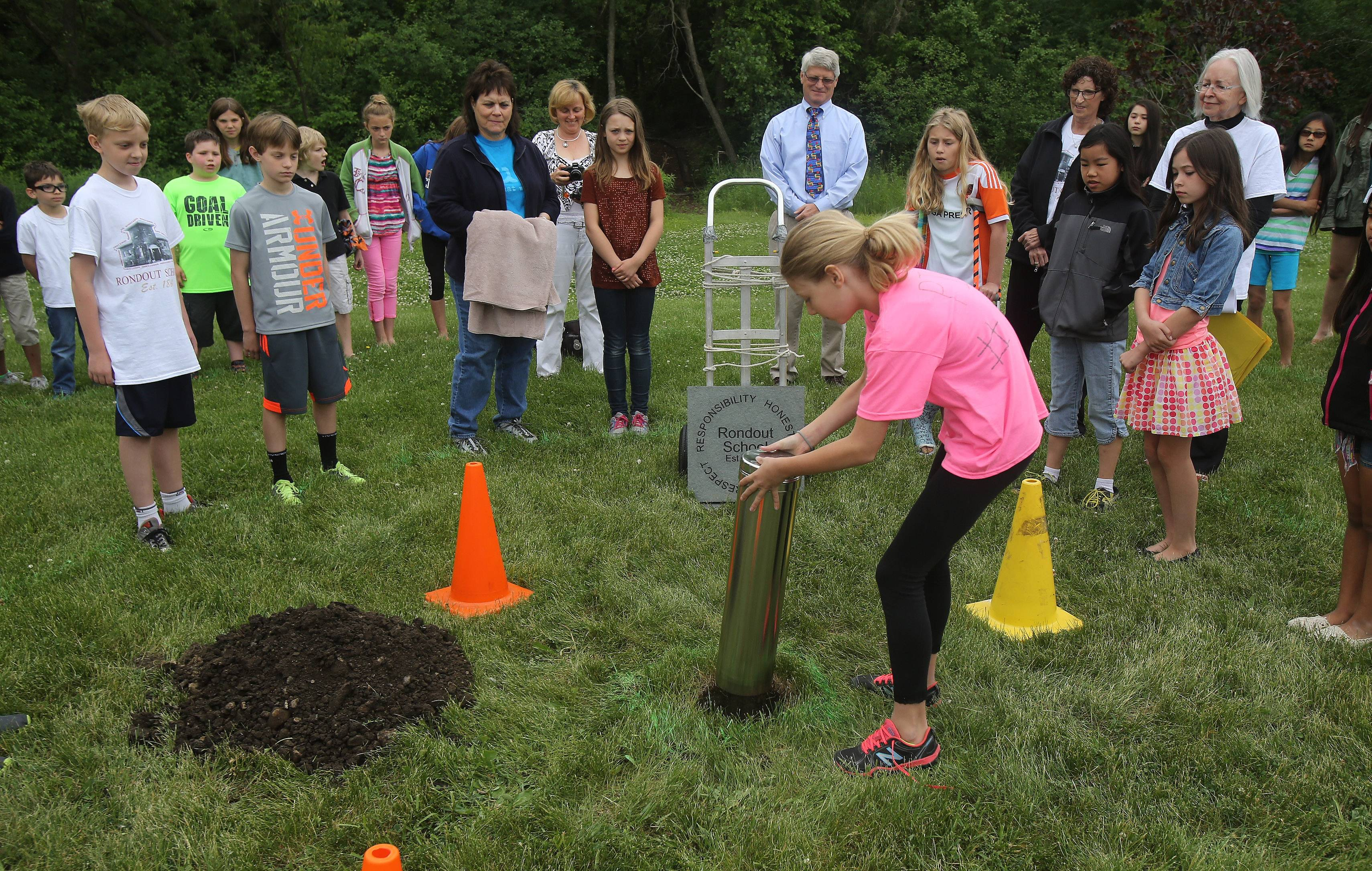 Rondout Elementary School fifth-grader Pia Bettridge puts a time capsule in the ground as part of the school's sesquicentennial celebration. Some of the items inside included a flash drive, cellphone, newspaper, Post-it's, a Toobaloo and the school mascot Falcon toy.