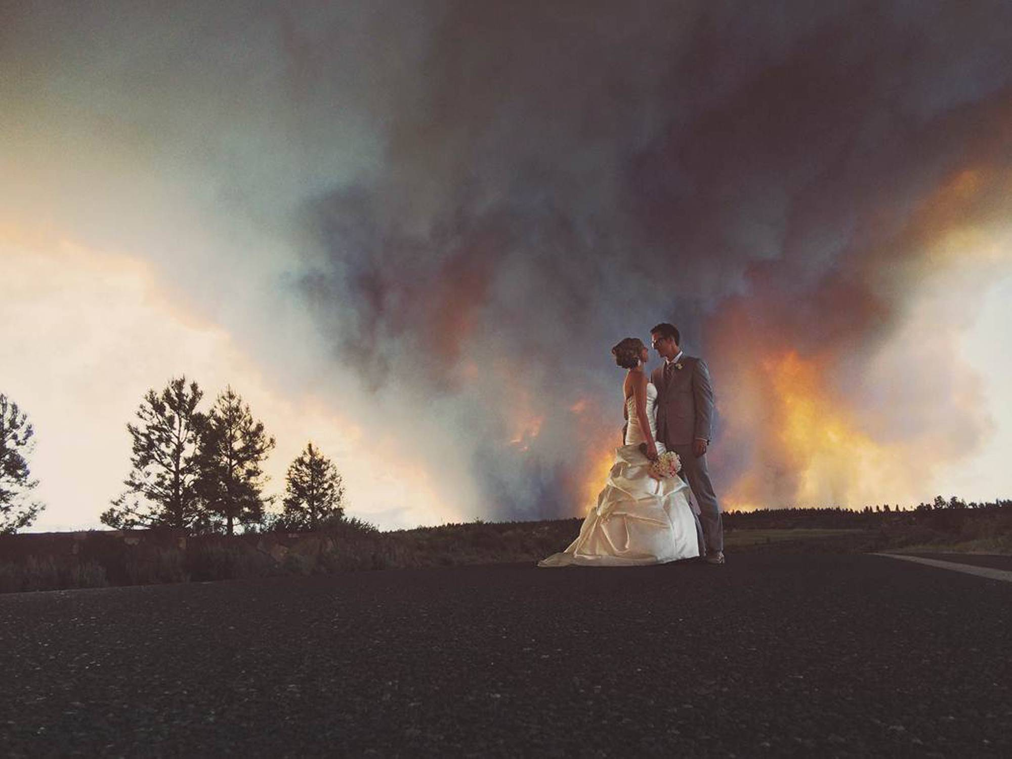 Newlyweds Michael Wolber and April Hartley pose for a picture near Bend, Ore., as a wildfire burns in the background. Because of the approaching fire, the minister conducted an abbreviated ceremony and the wedding party was evacuated to a downtown Bend park for the reception.