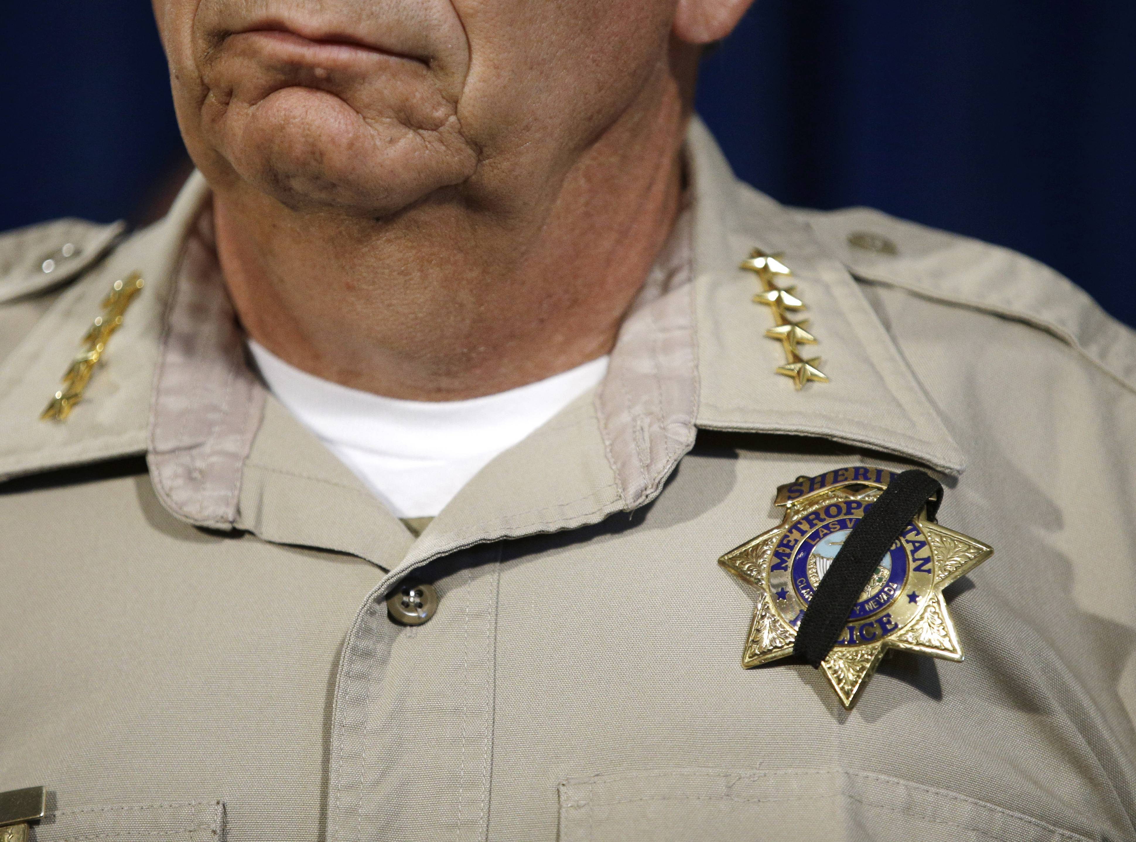 Las Vegas Sheriff Doug Gillespie wears a black band across his badge during a news conference, Monday, June 9, 2014, in Las Vegas.