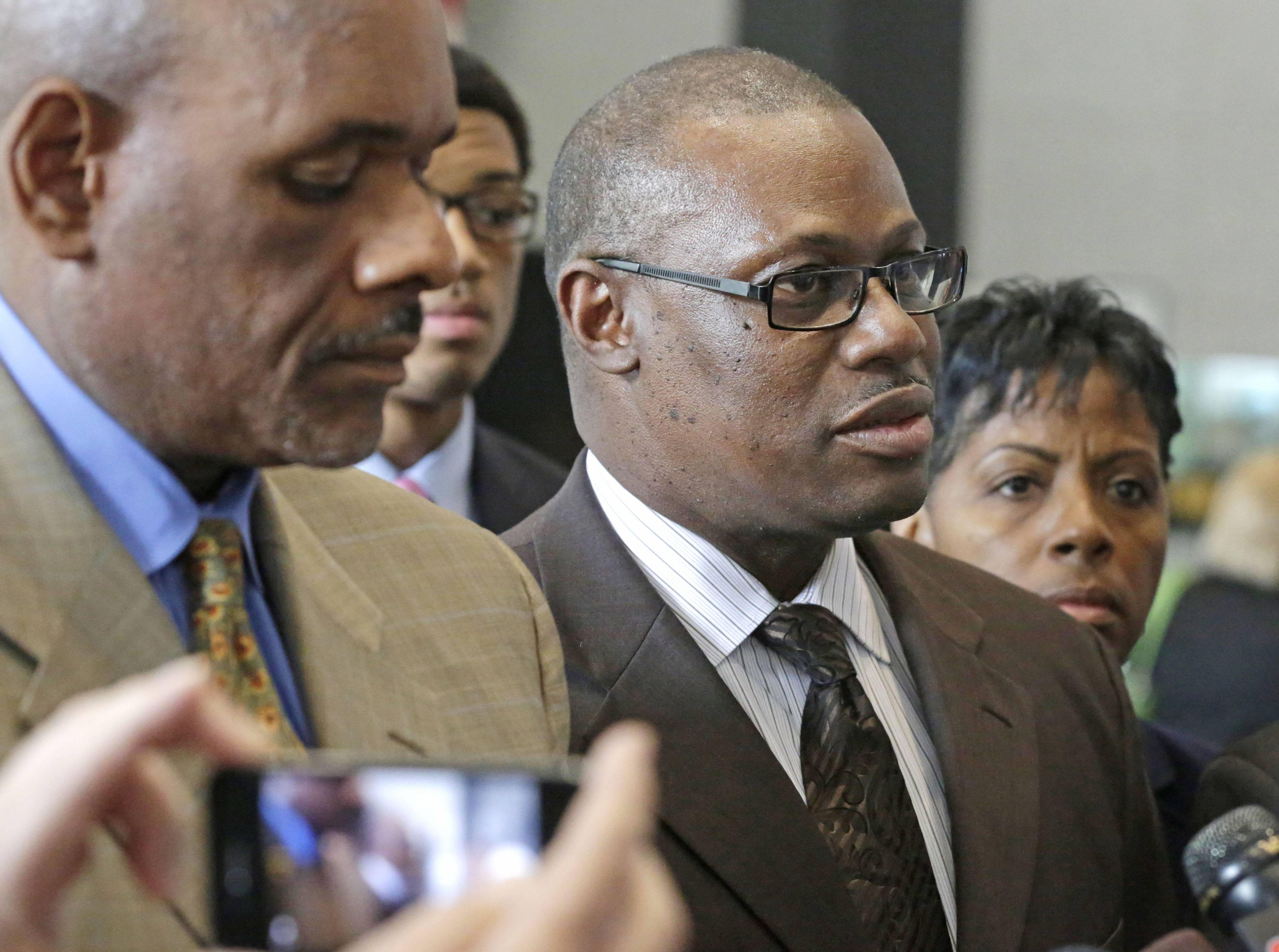 State Rep. Derrick Smith, center, speaks to reporters Tuesday at the federal building in Chicago.