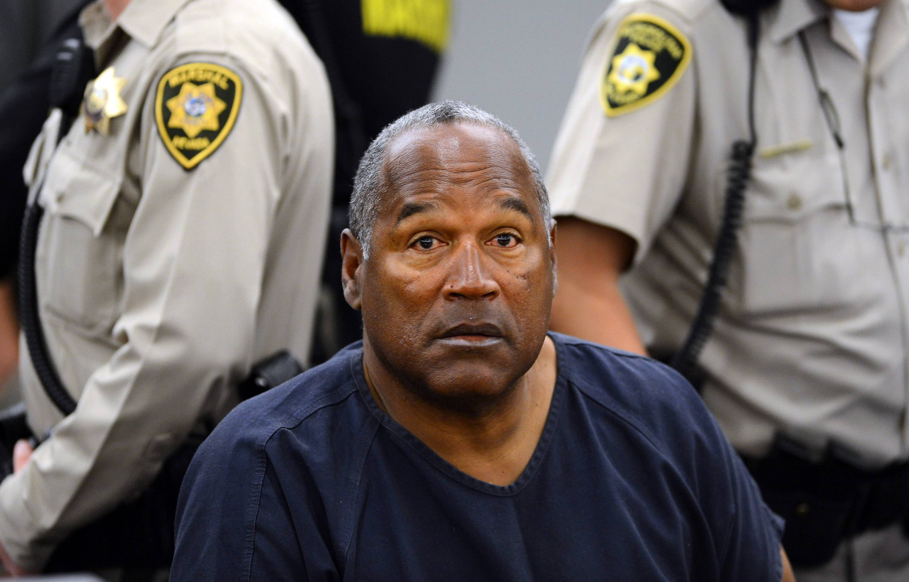 In this May 14, 2013 file photo, O.J. Simpson sits during a break on the second day of an evidentiary hearing in Clark County District Court in Las Vegas. Simpson is serving nine to 33 years in prison for his 2008 conviction in the armed robbery of two sports memorabilia dealers in a Las Vegas hotel room.