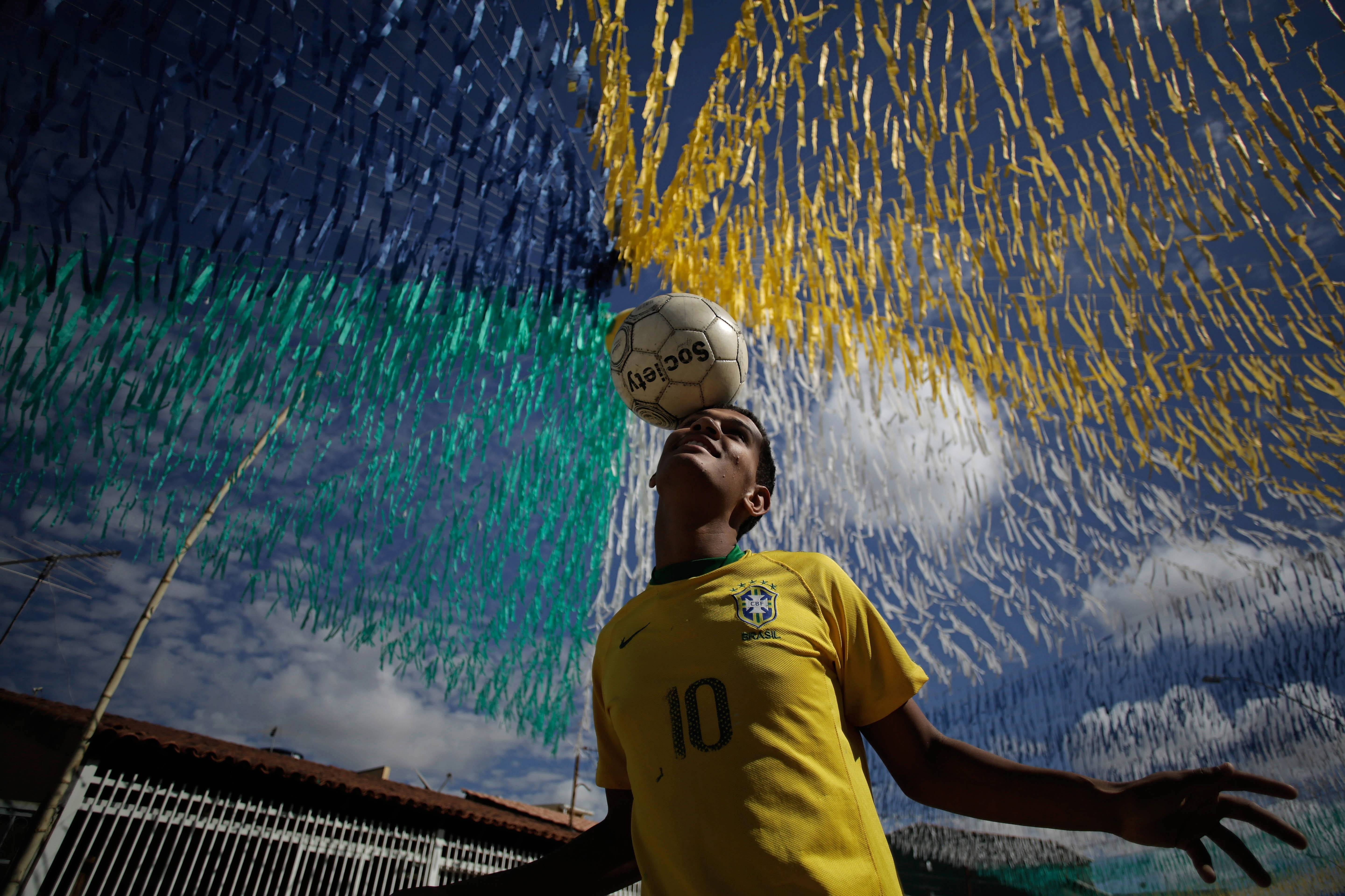In this June 4 photo, Joao Paulo, 16, plays ball in a street decorated for the upcoming World Cup in the Ceilandia suburb of Brasilia, Brazil. The international soccer tournament is set to begin next week.