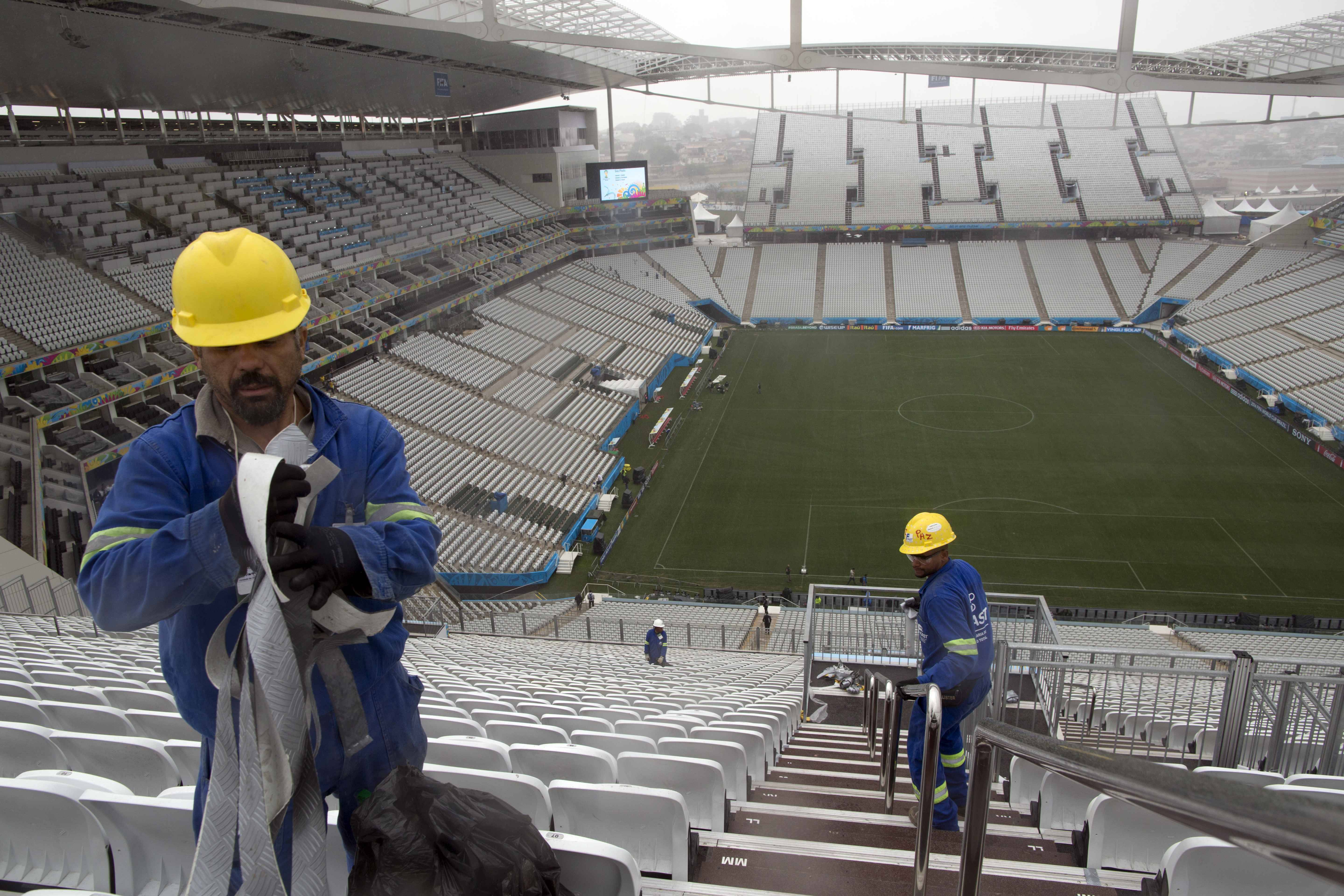 Workers clean the stairs at Arena Corinthians stadium in Sao Paulo, Brazil, Wednesday, June 11, 2014. The World Cup soccer tournament starts Thursday. (AP Photo/Rodrigo Abd)