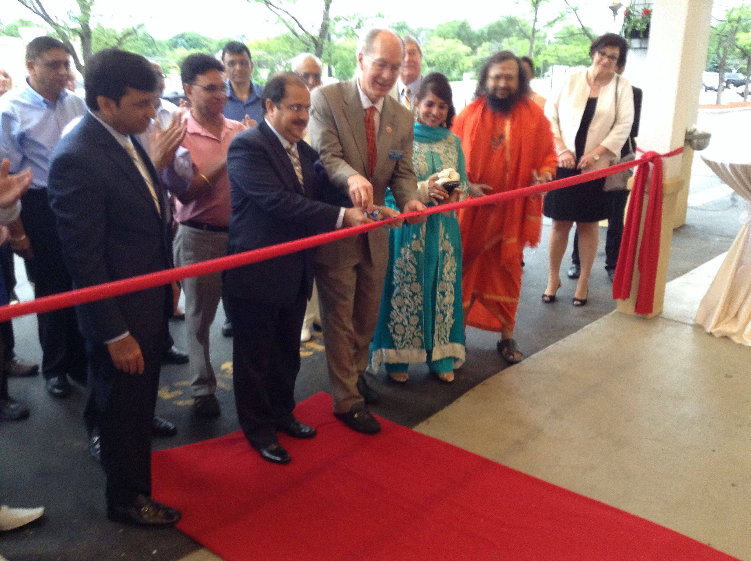 Baig on the left and with Congressman Bill Foster and Ausaf Sayeed, counsel general of India, cutting the ribbon.
