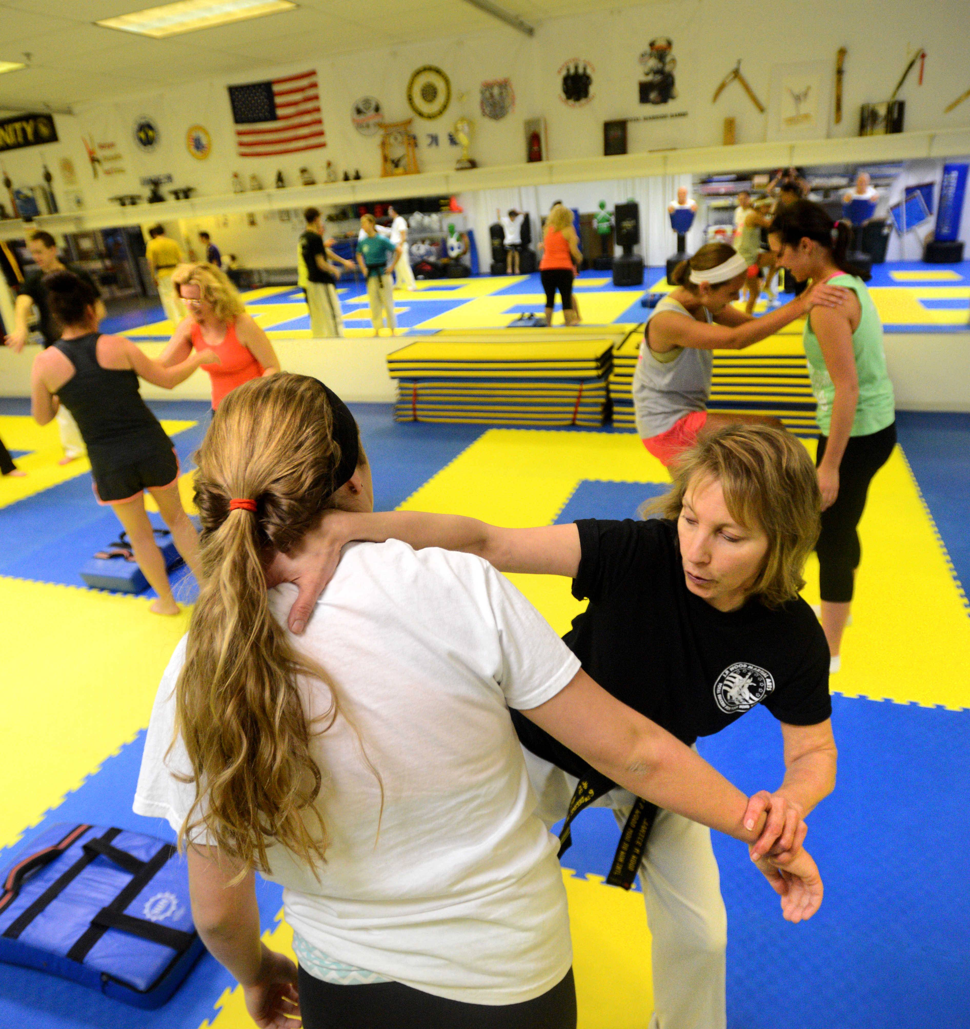 Instructor Jan Wood performs an escape move on Taylor Delapa of Palatine.