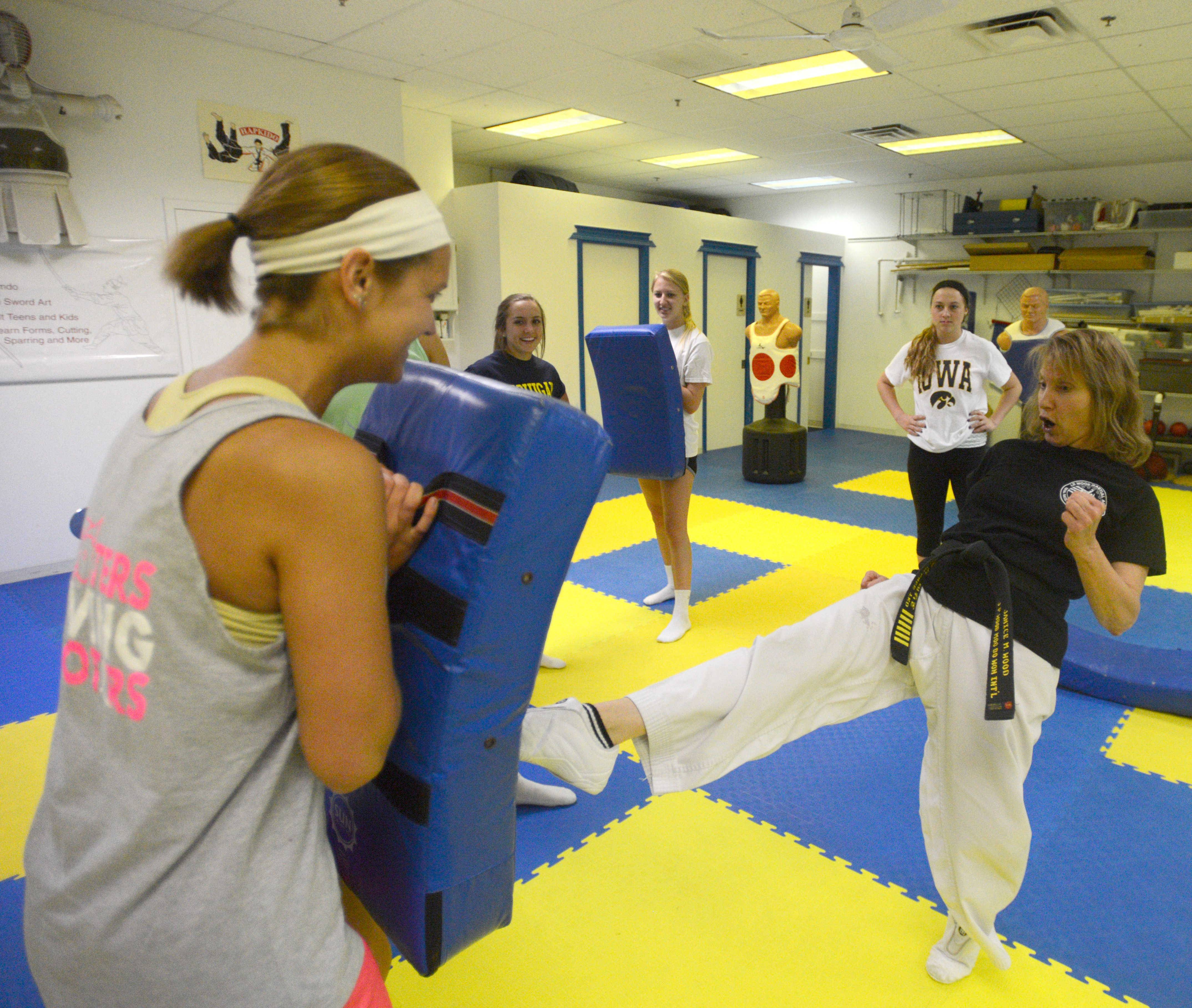 Instructor Jan Wood demonstrates a kick with student Rachel Wittel of Palatine.