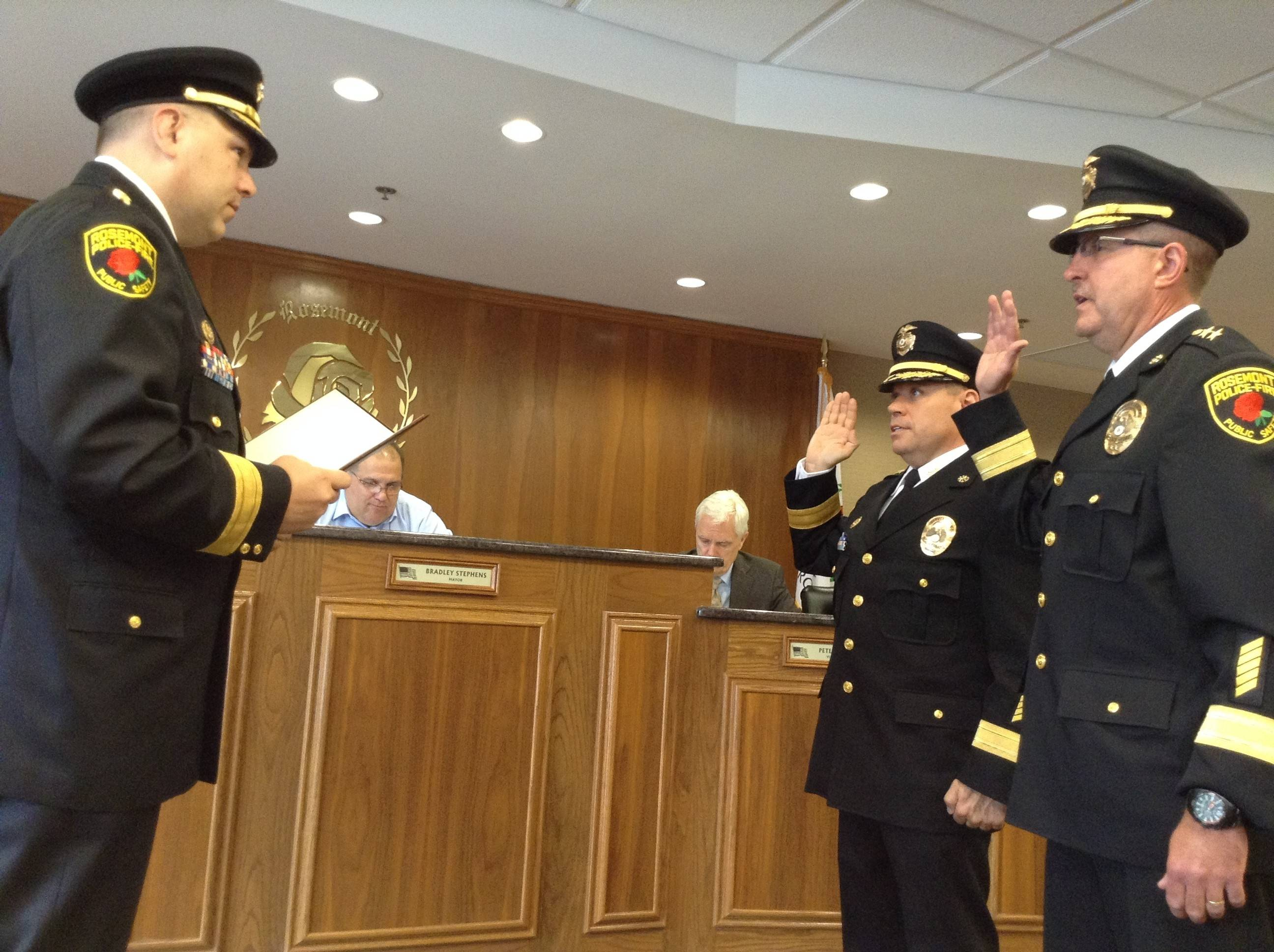 Rosemont Public Safety Department Chief Don Stephens III, left, swears in Deputy Chiefs Kevin Kukulka and John Aichinger at Wednesday's village board meeting.