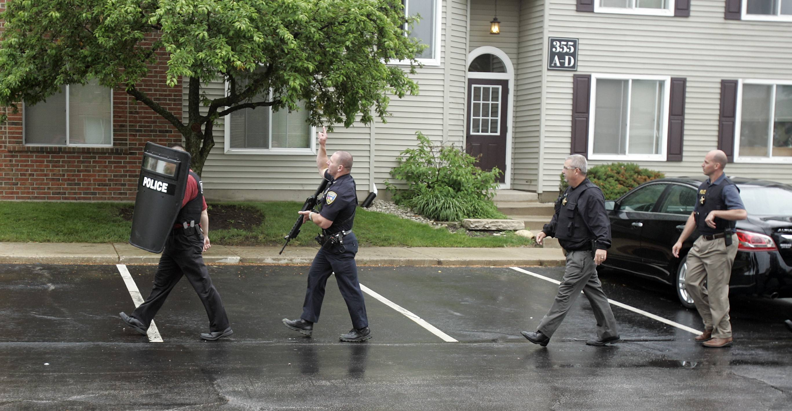 Officers from St. Charles, Geneva, Batavia and Sugar Grove move into position Wednesday at Ashford At Geneva Apartment Homes to apprehend two people suspected of several robberies.
