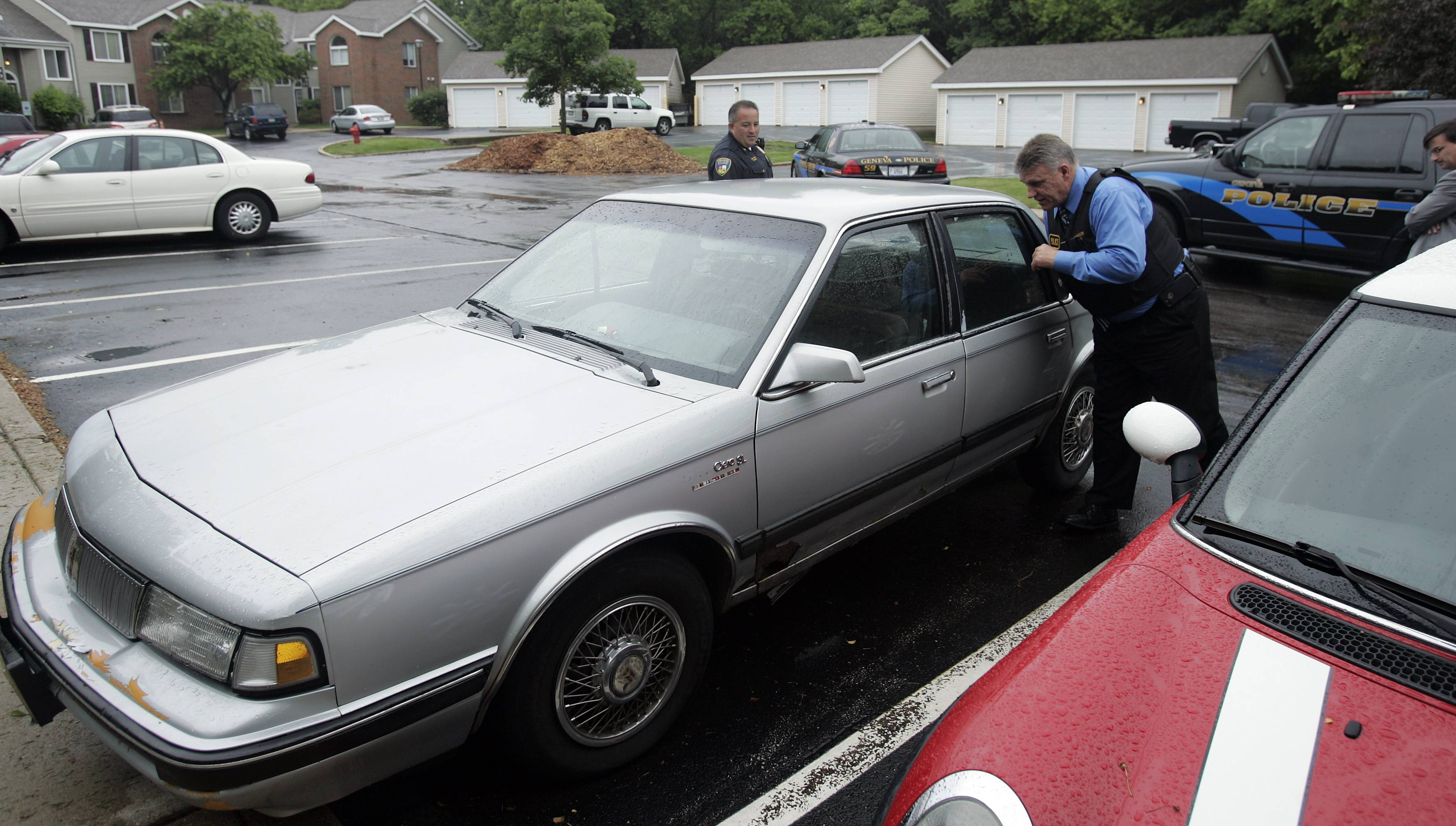 St. Charles police Cmdr. Jerry Gatlin looks over a vehicle that might have been used by people suspected in a series of local robberies, the most recent of which was early Wednesday in Batavia. The car was found at a Geneva apartment complex.