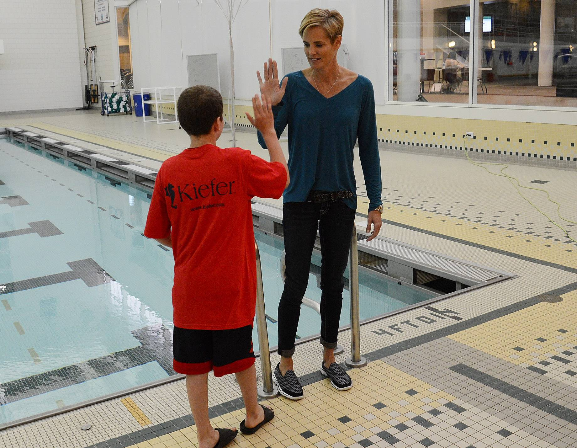 Olympic swimmer Dara Torres gives a high-five to Tamer Dalloul of Long Grove while getting his picture taken prior to Torres talking about the dangers of bacterial meningitis while visiting Stevenson High School Tuesday night.