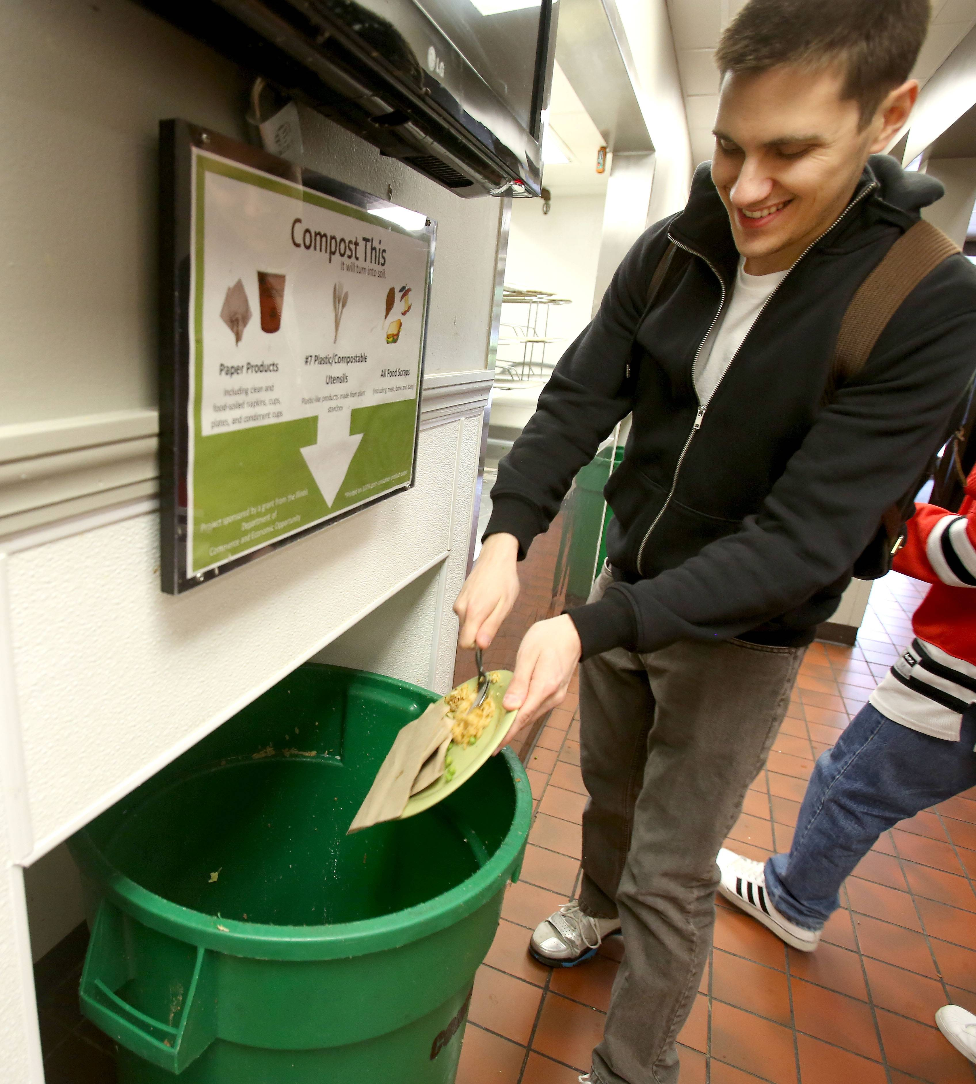 Sophomore Max Kachinske throws his leftovers in the compost bin in the cafeteria at Kaufman Hall at North Central College in Naperville. Students have been composting there for three years.