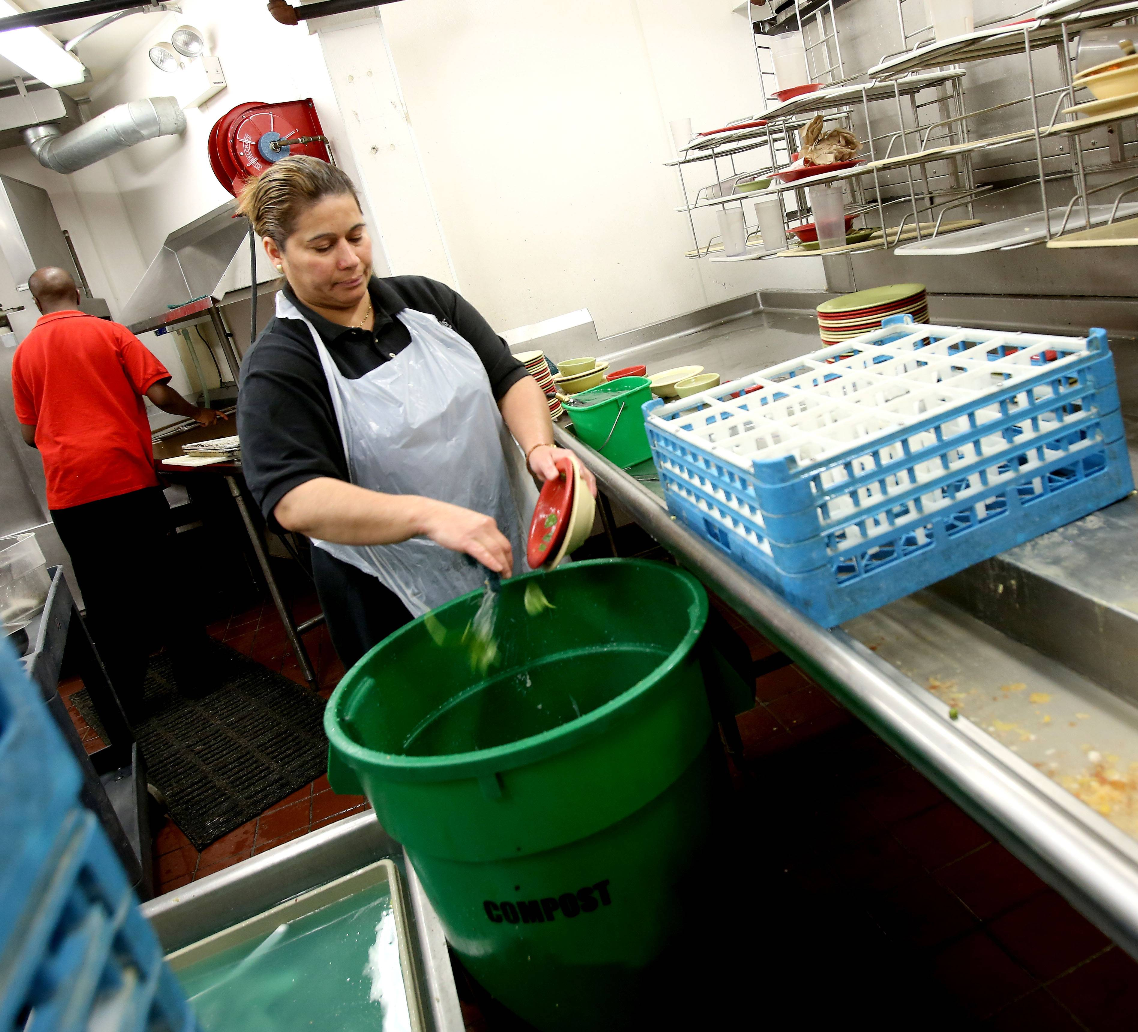 Laura Guzman adds food scraps students miss to the compost pile in the cafeteria at North Central College in Naperville.